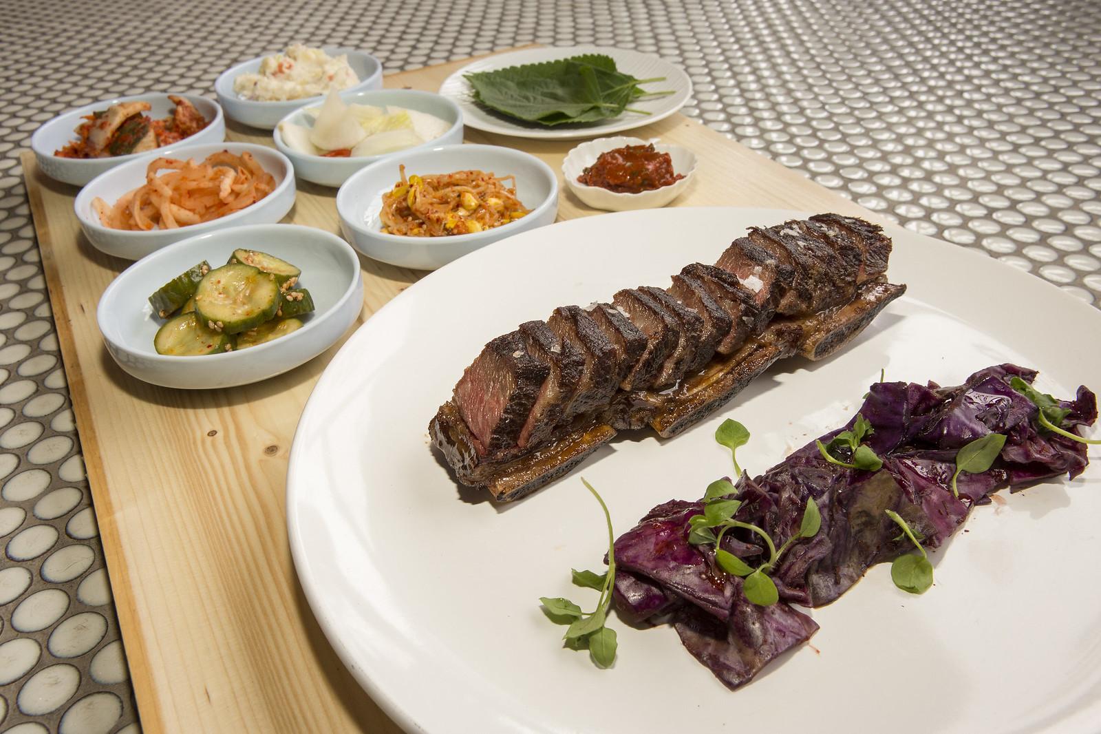 A platter of Korean short ribs with color banchan.