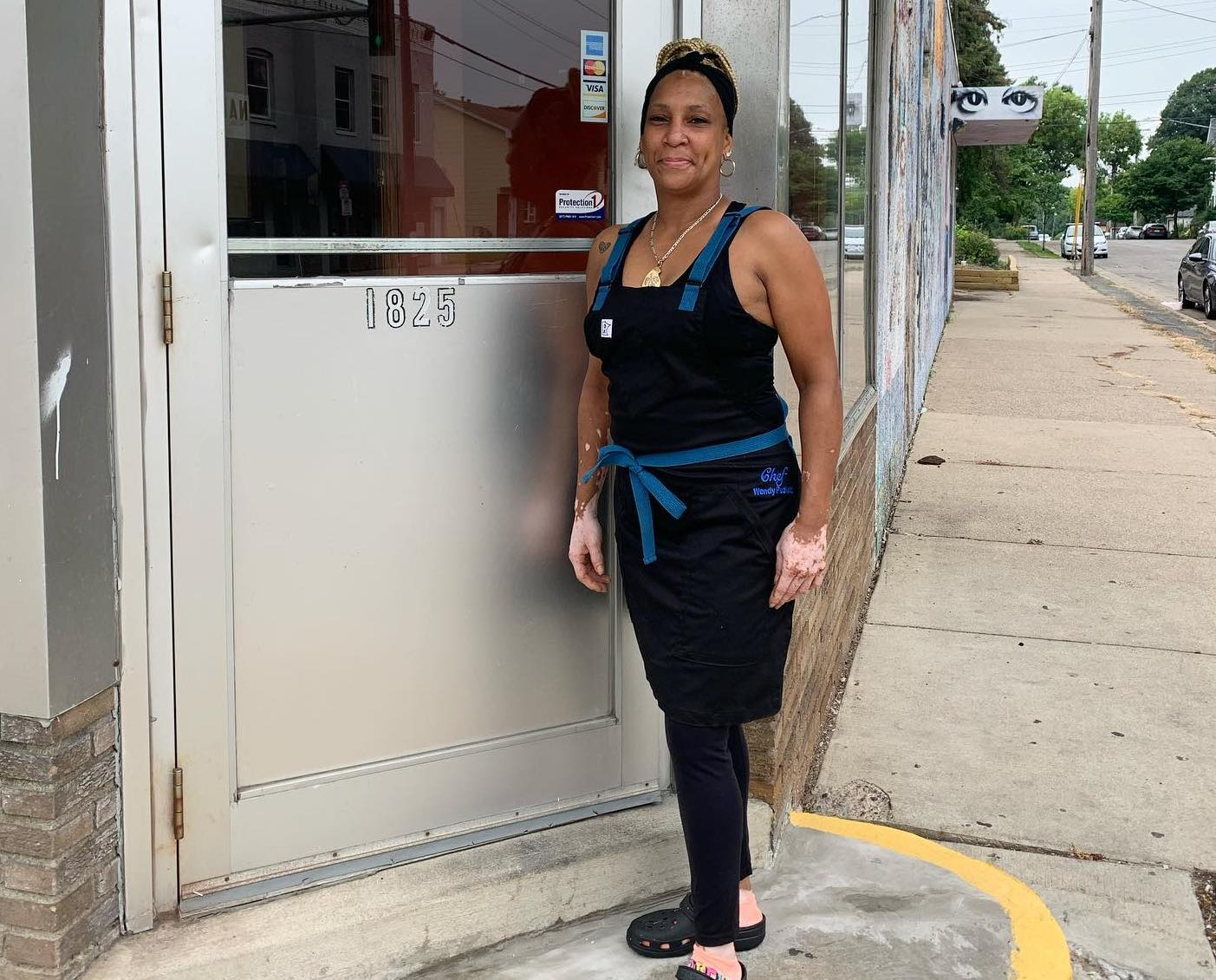 Chef Wendy Puckett stands outside 1825 Glenwood, the new location for her restaurant, arms crossed, wearing a Project Black and Blue Craftmade Apron, arms at her sides, a small smile playing at her lips