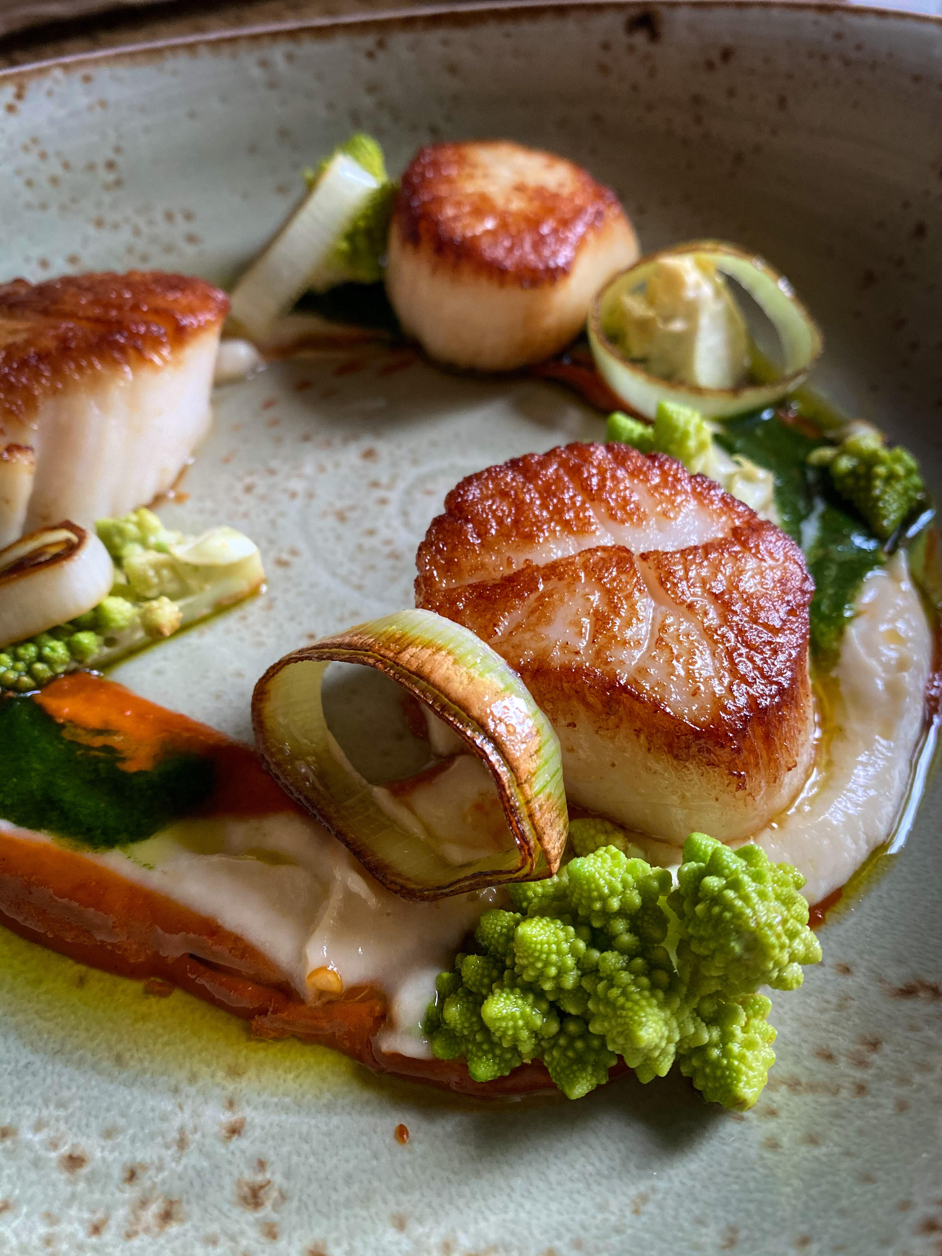 Scallops with Walla Walla onion purée and charred leeks on a white dish