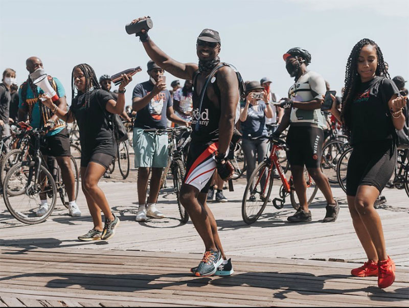 A group of people dancing on a beach boardwalk