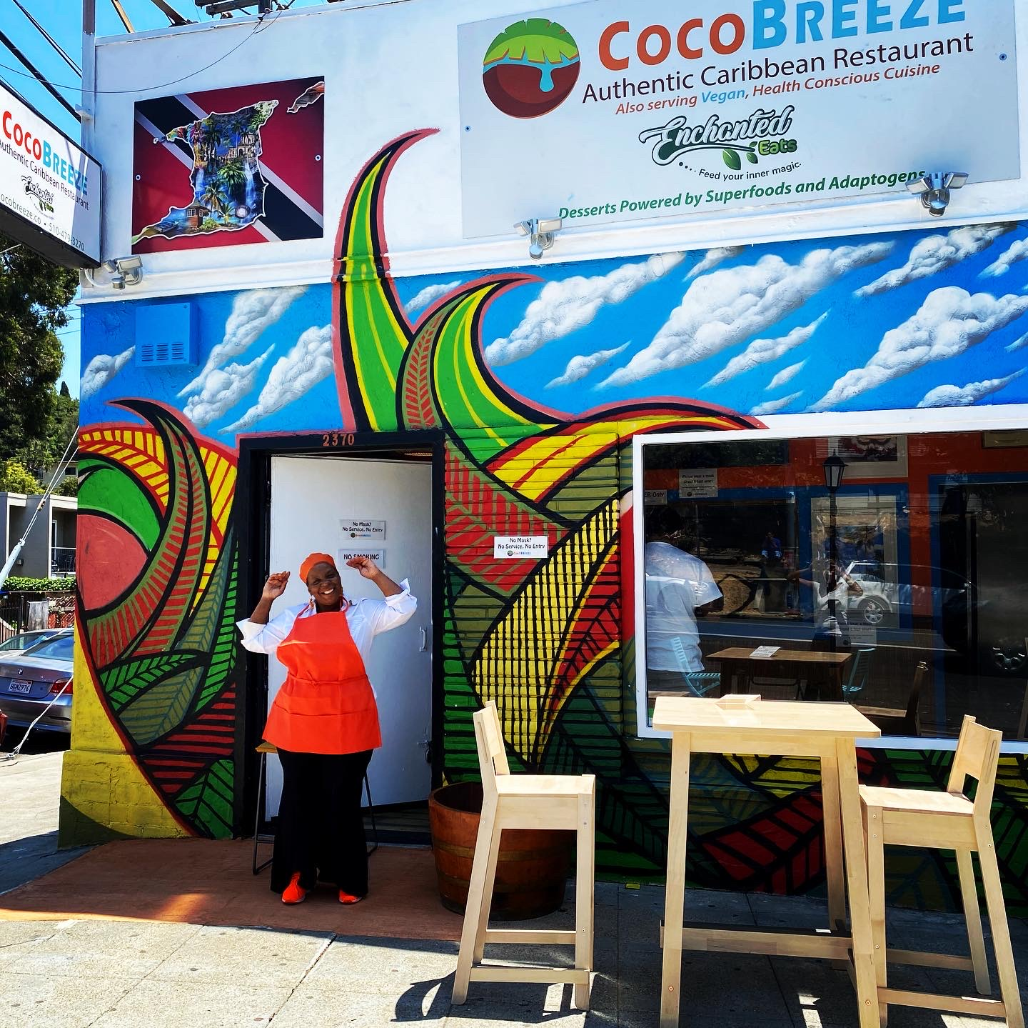 The chef stands in front of the restaurant, whose facade is decorated with a colorful tropical mural, with her arms raised in triumph
