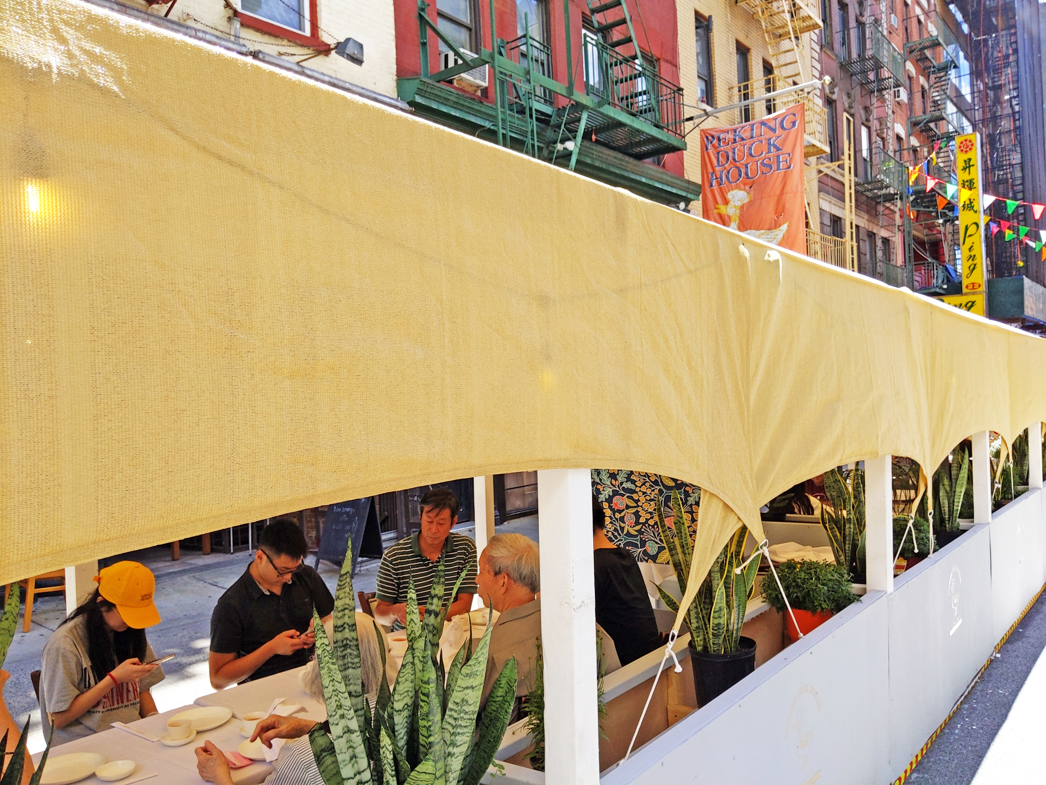 A yellow awning protects the tables in an outdoor seating area in the foreground while the sign of the restaurant featuring a duck is visible in the background.