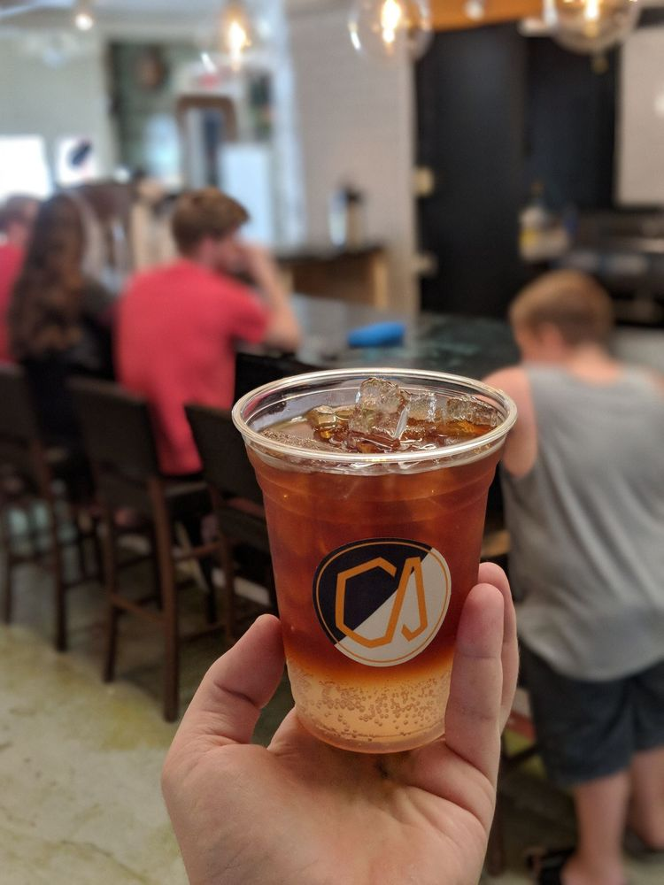 A hand holding a sparkling iced coffee concoction from Academy Coffee in front of three people sitting at the bar beyond