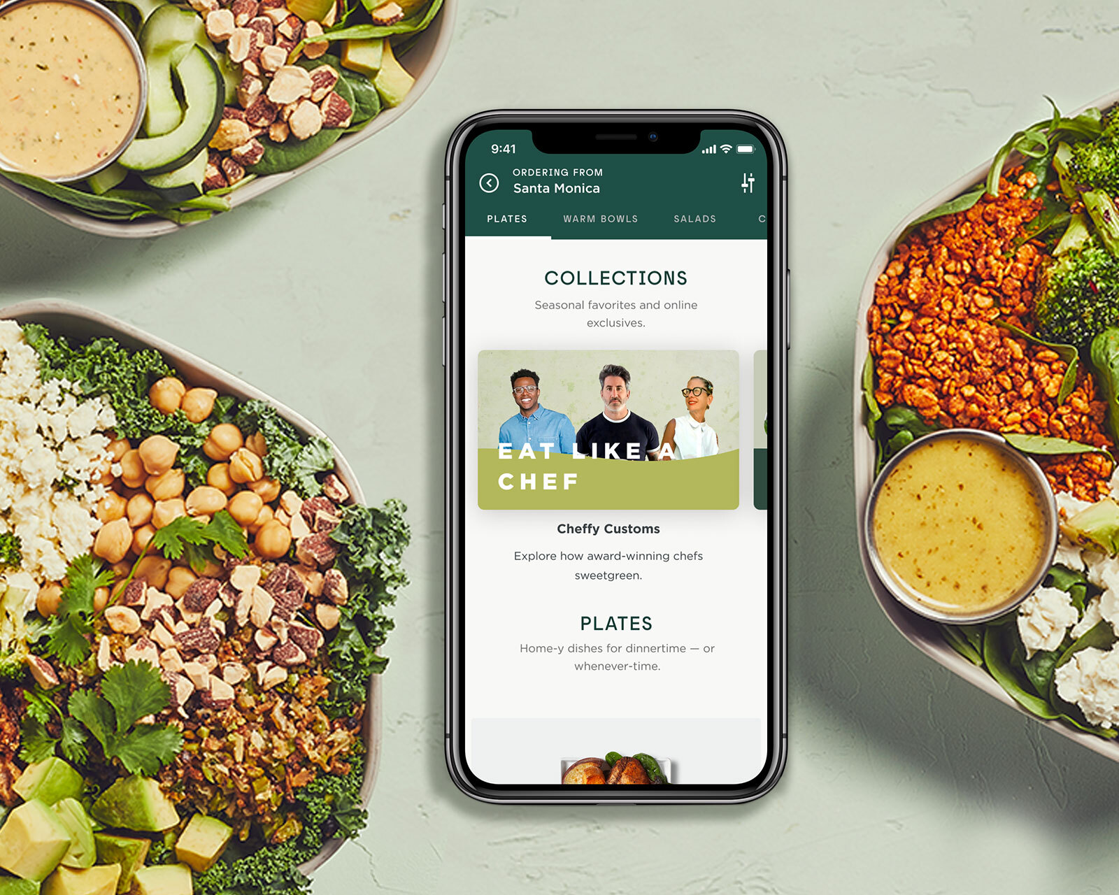 Three salad bowls arranged around a phone with the Sweetgreen app open on a white background