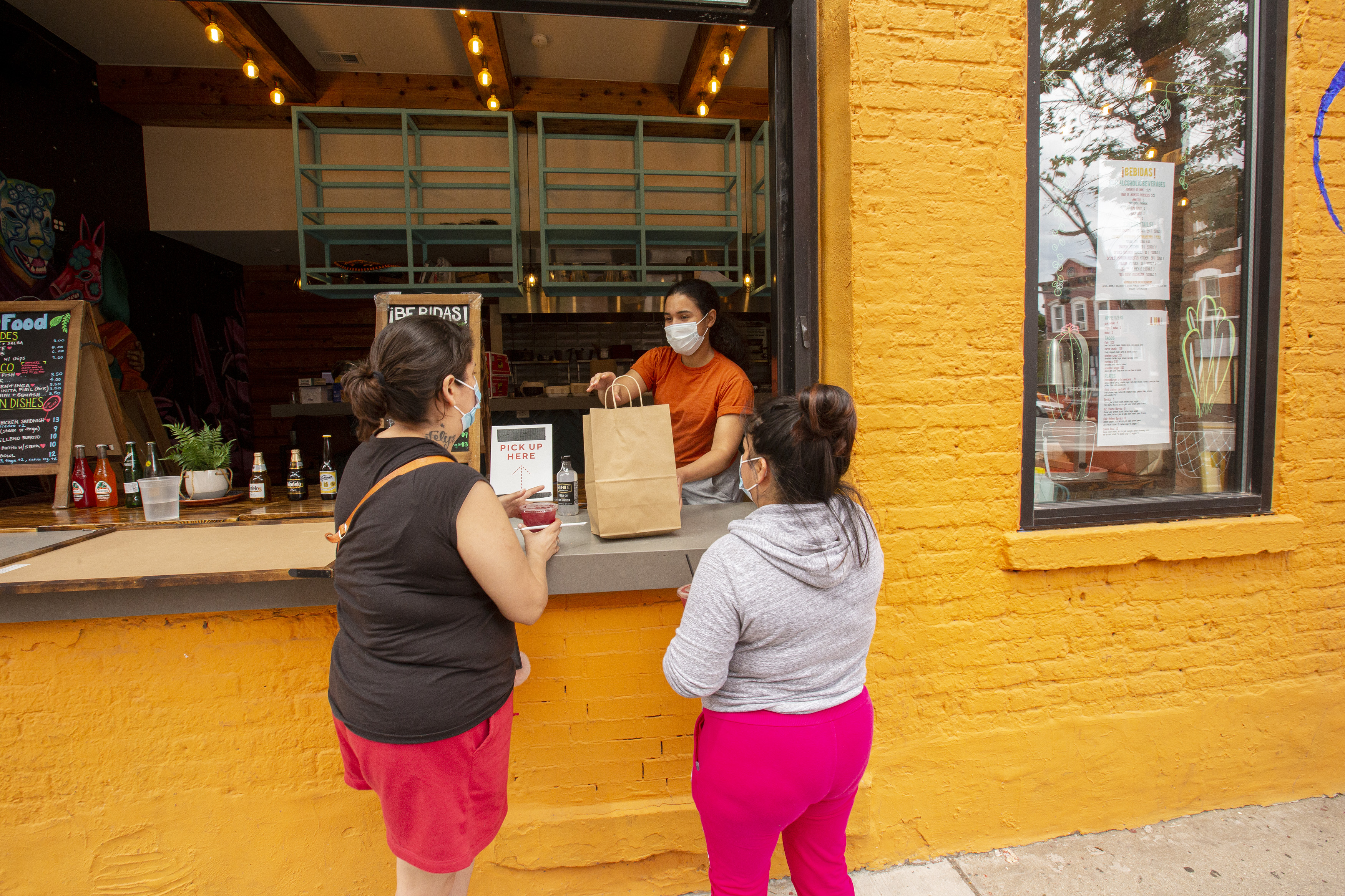 A server in a mask hands a large brown paper bag to two women wearing masks through a large walk-up window.
