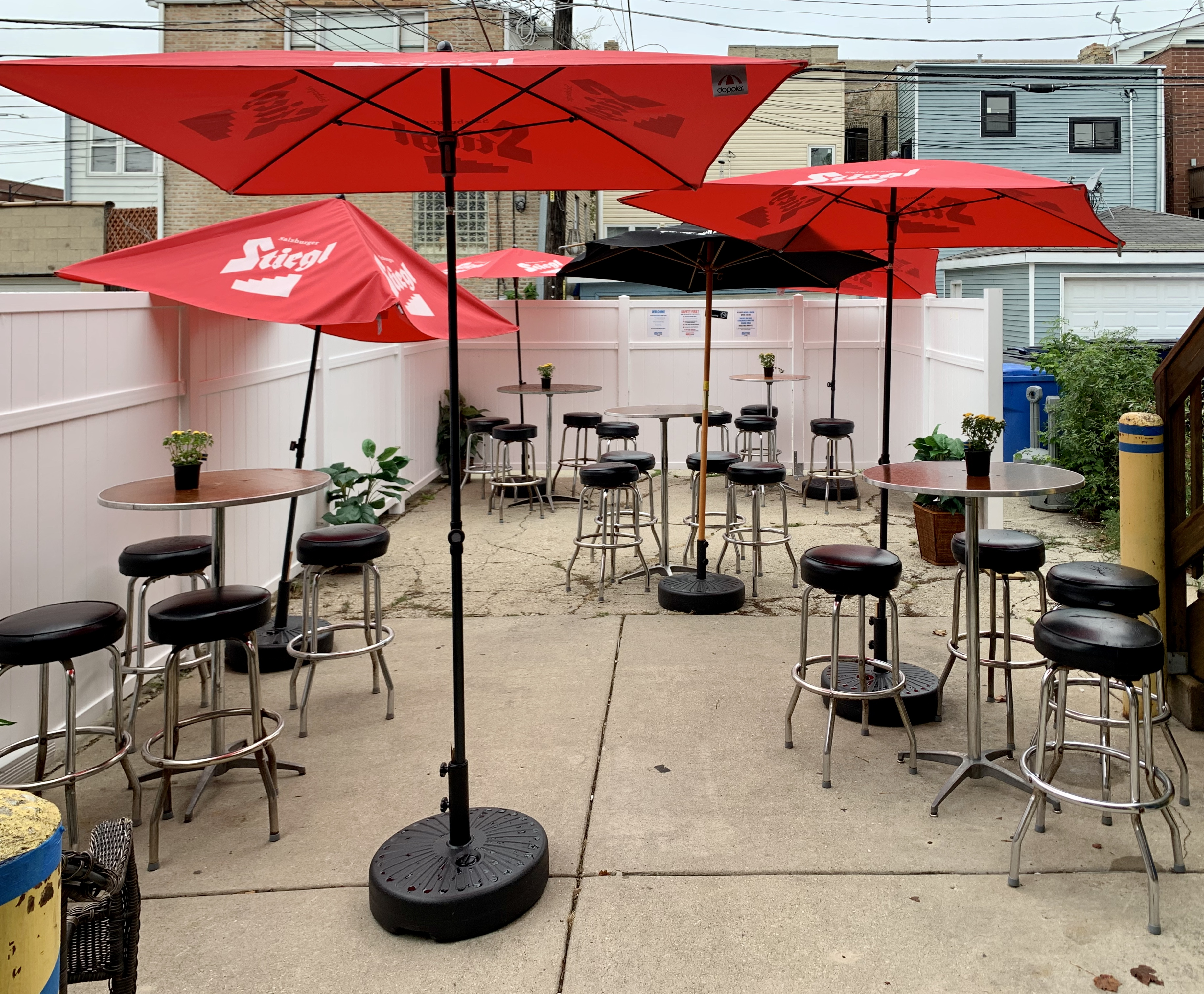 A small paved outdoor patio with tables and stools