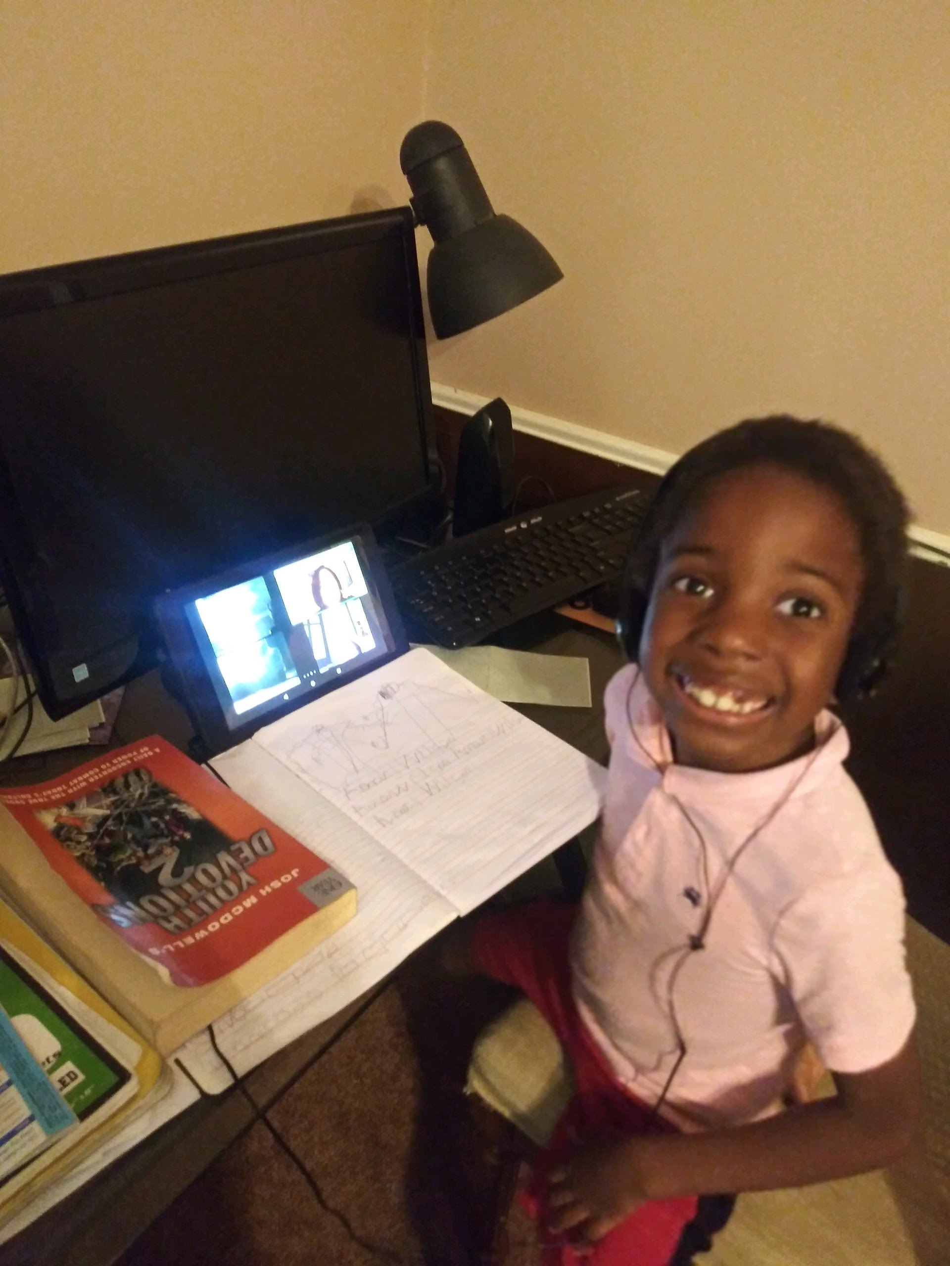 Six-year-old child practices writing his name with his teacher via video conference
