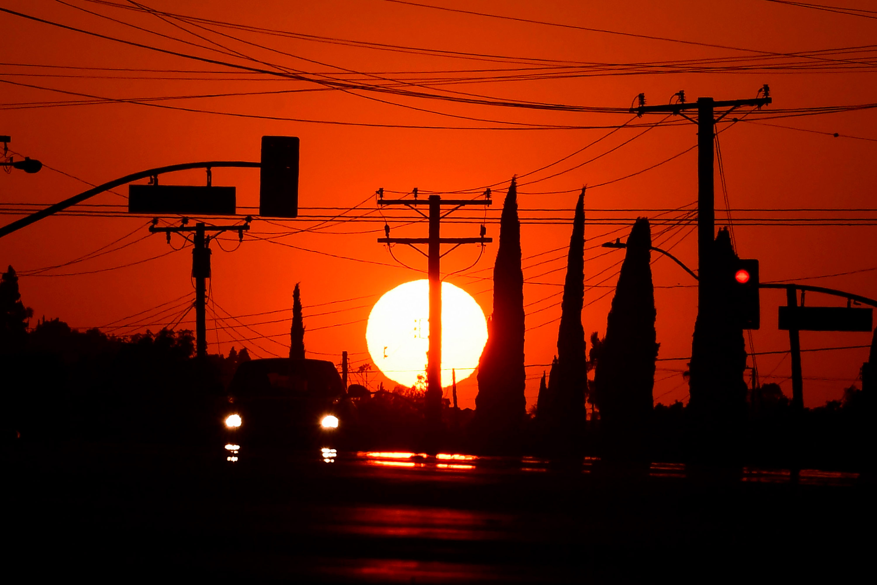 The sun sets behind power lines in Los Angeles, California on September 3, 2020, ahead of a heatwave to arrive September 4 through the Labour Day weekend prompting a statewide flex alert.