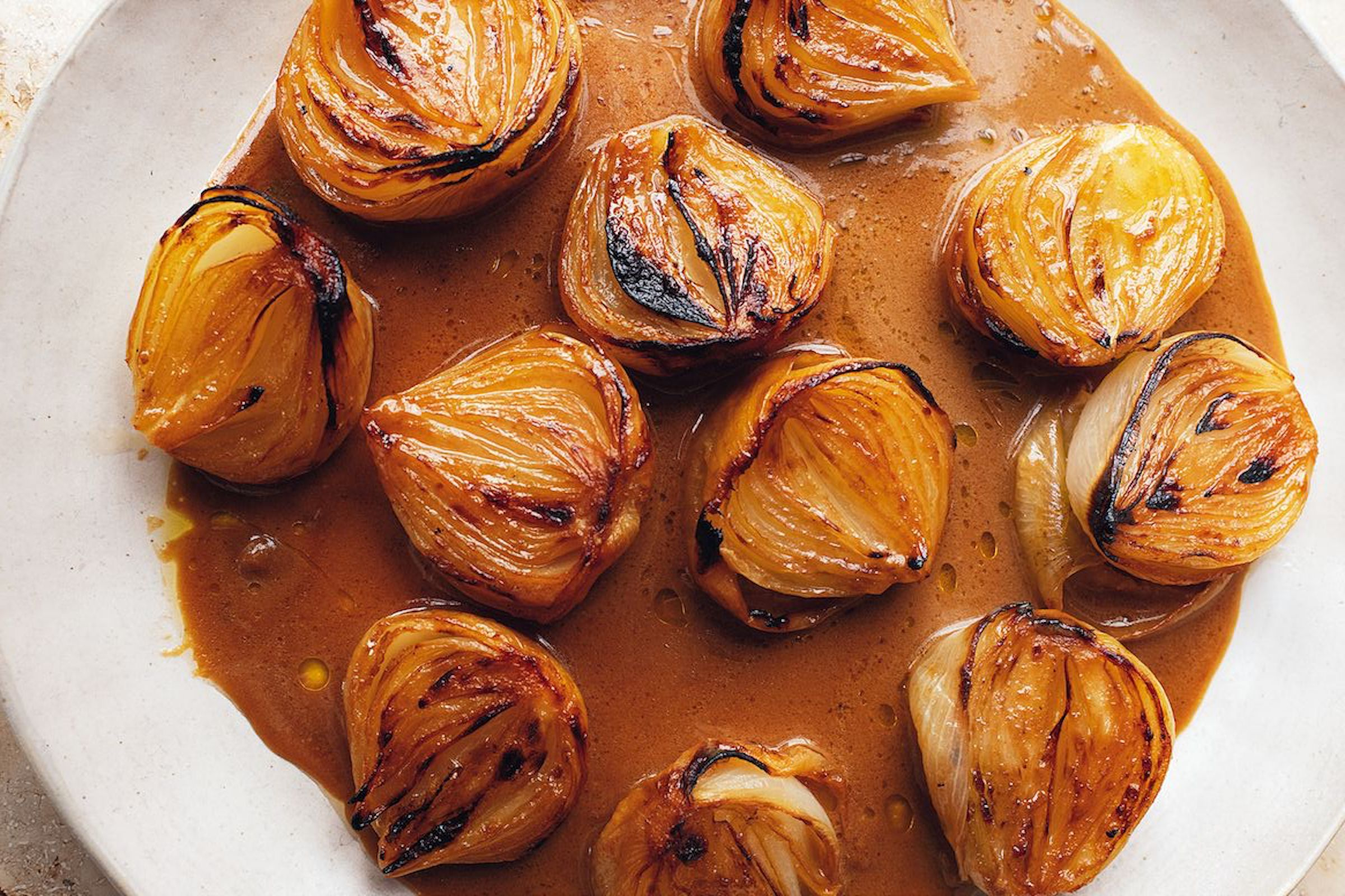 A platter of baked, slightly charred onions in a deep brown miso bitter sauce, served on a large white platter; it's a recipe from Yotam Ottolenghi, in Flavour