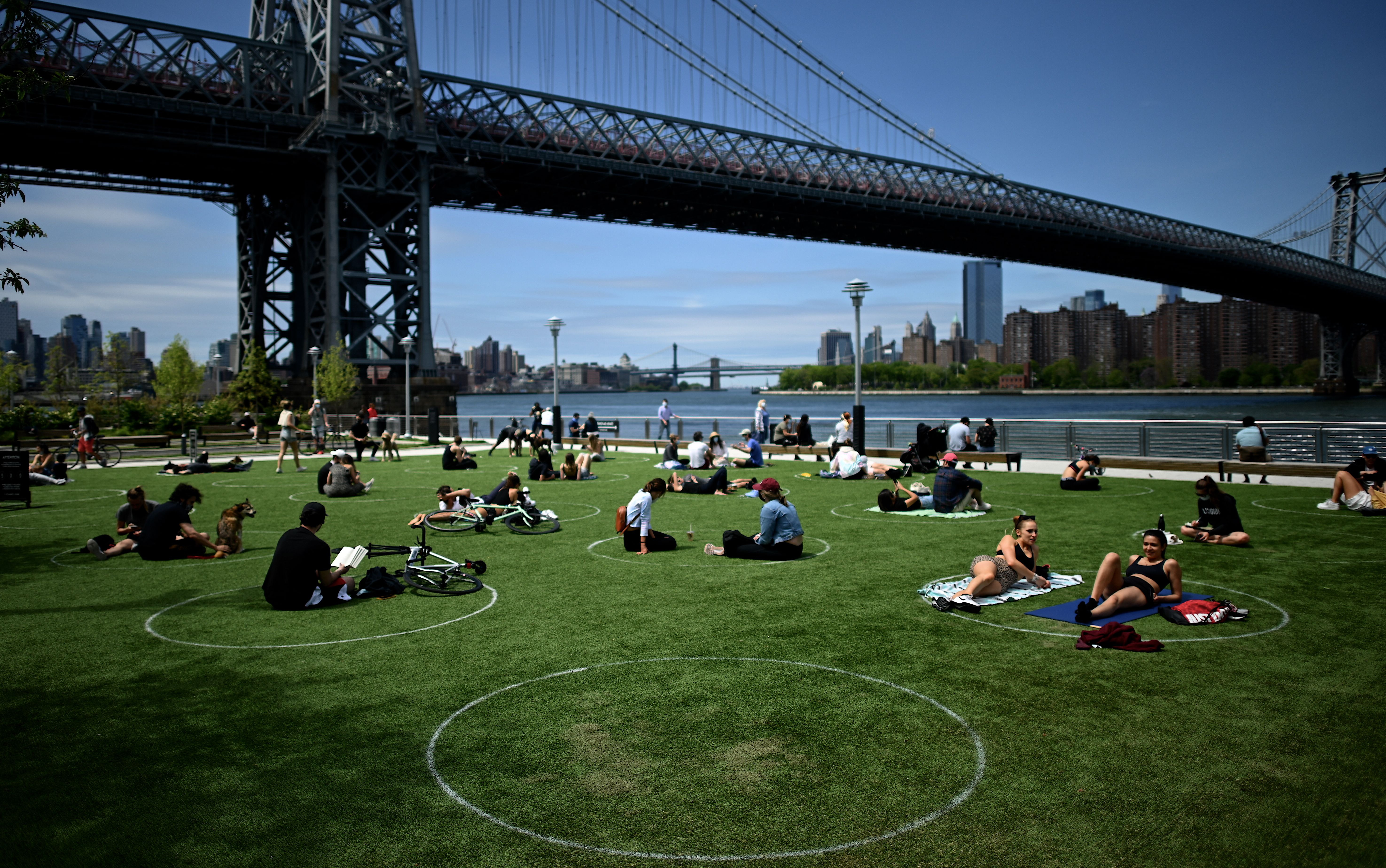 People sit within social distance circles on grass in a park beneath the Brooklyn Bridge.