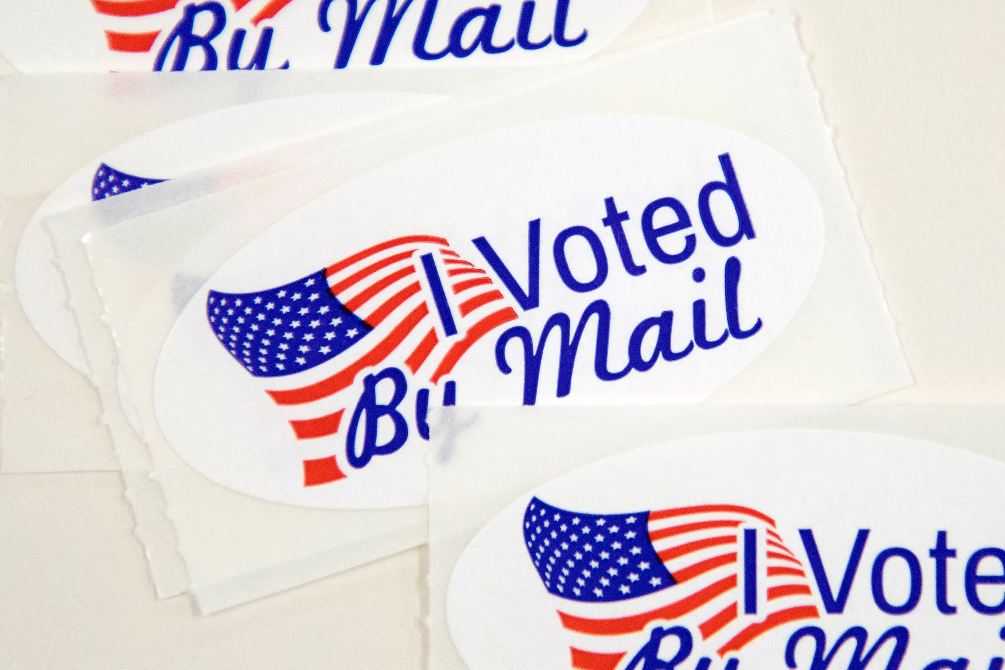 "A roll of stickers that read ""I voted by mail."""