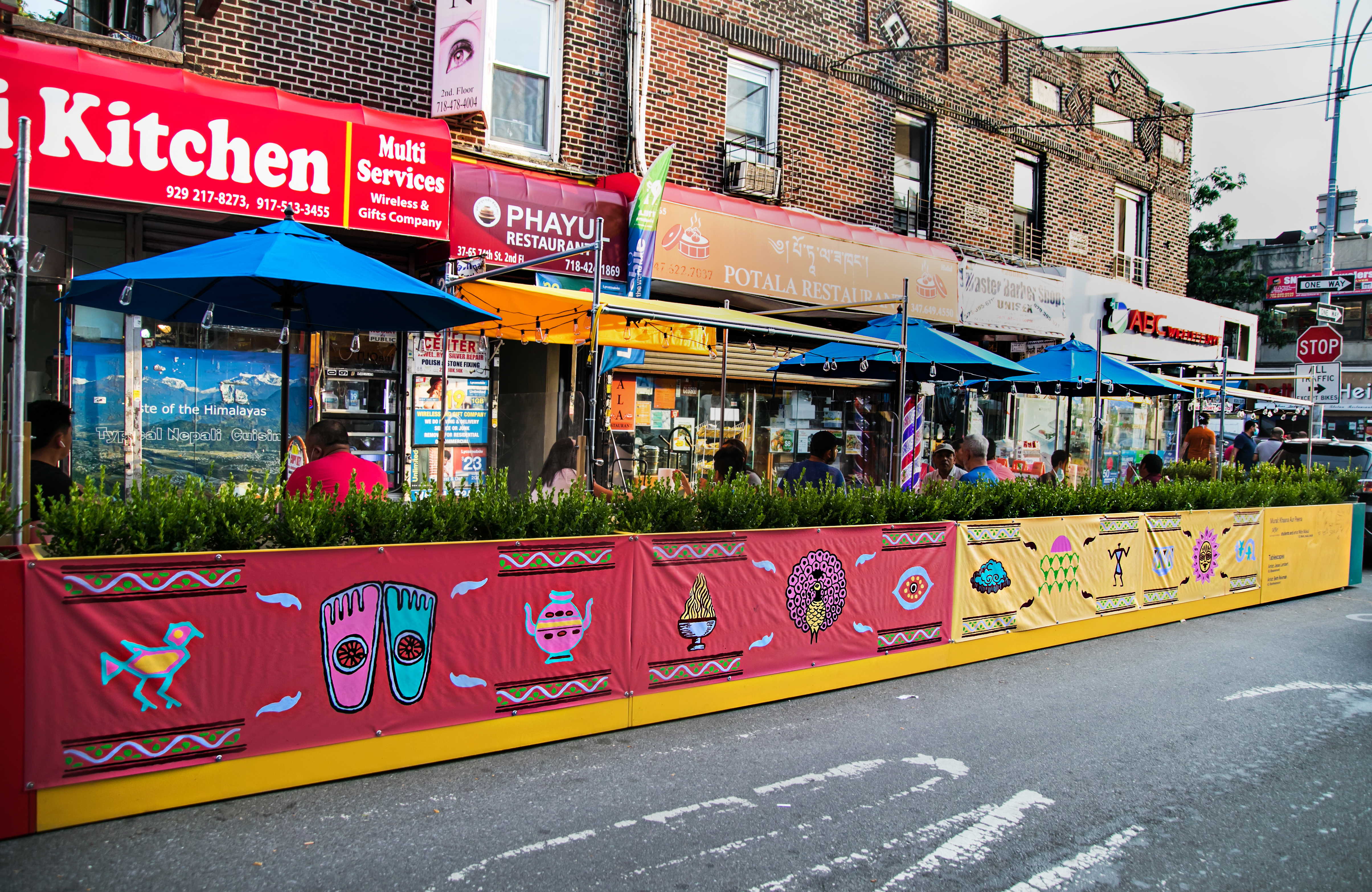 An exterior view of outdoor dining platforms built for restaurants during coronavirus. These brightly colored streeteries were designed by DineOut NYC.