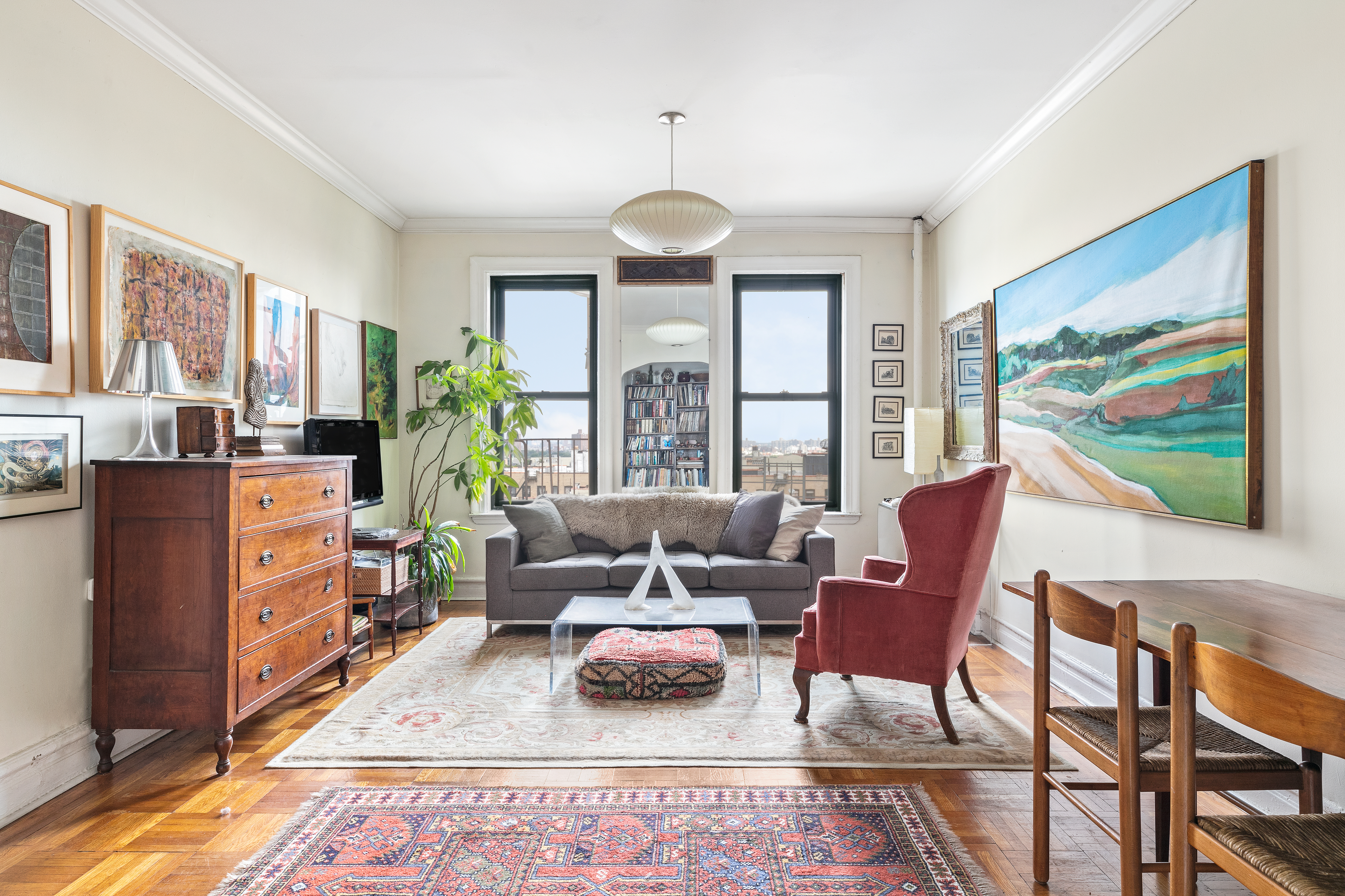 A living room inside a Prospect Heights, Brooklyn, apartment with two windows, a dark grey couch, base and crown moldings, beige walls, and hardwood floors.