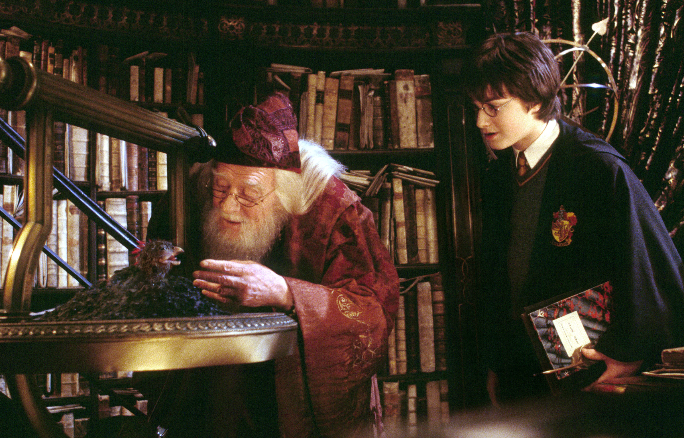 """Harry Potter (Daniel Radcliffe) watches as Professor Dumbledore (Richard Harris) feeds Fawkes the Phoenix in the movie, """"Harry Potter and the Chamber of Secrets."""""""