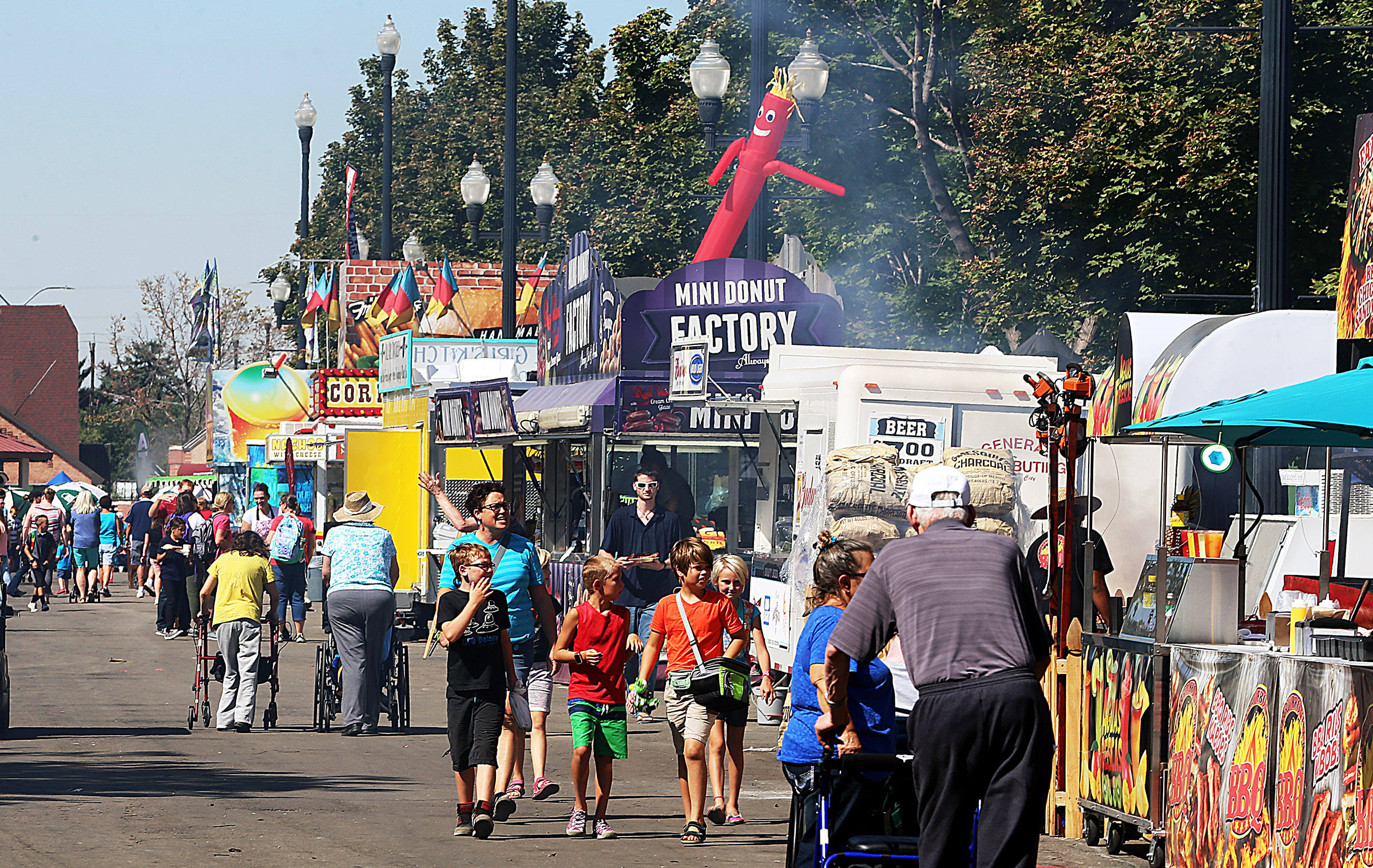 Fair attendees search out food options at the Utah State Fair in Salt Lake City on Monday, Sept. 11, 2017.