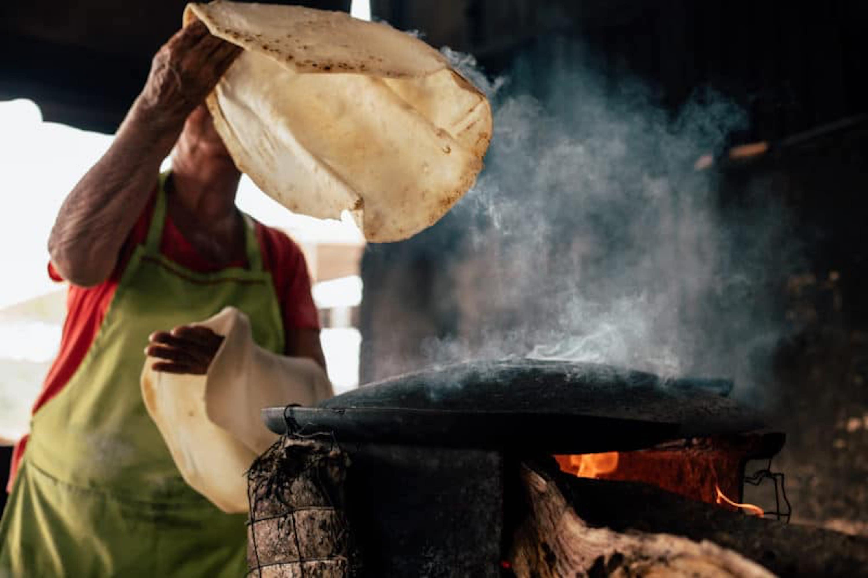A tortilla being flipped for a burrito over a smoking comal in Mexico on Taco Chronicles on Netflix