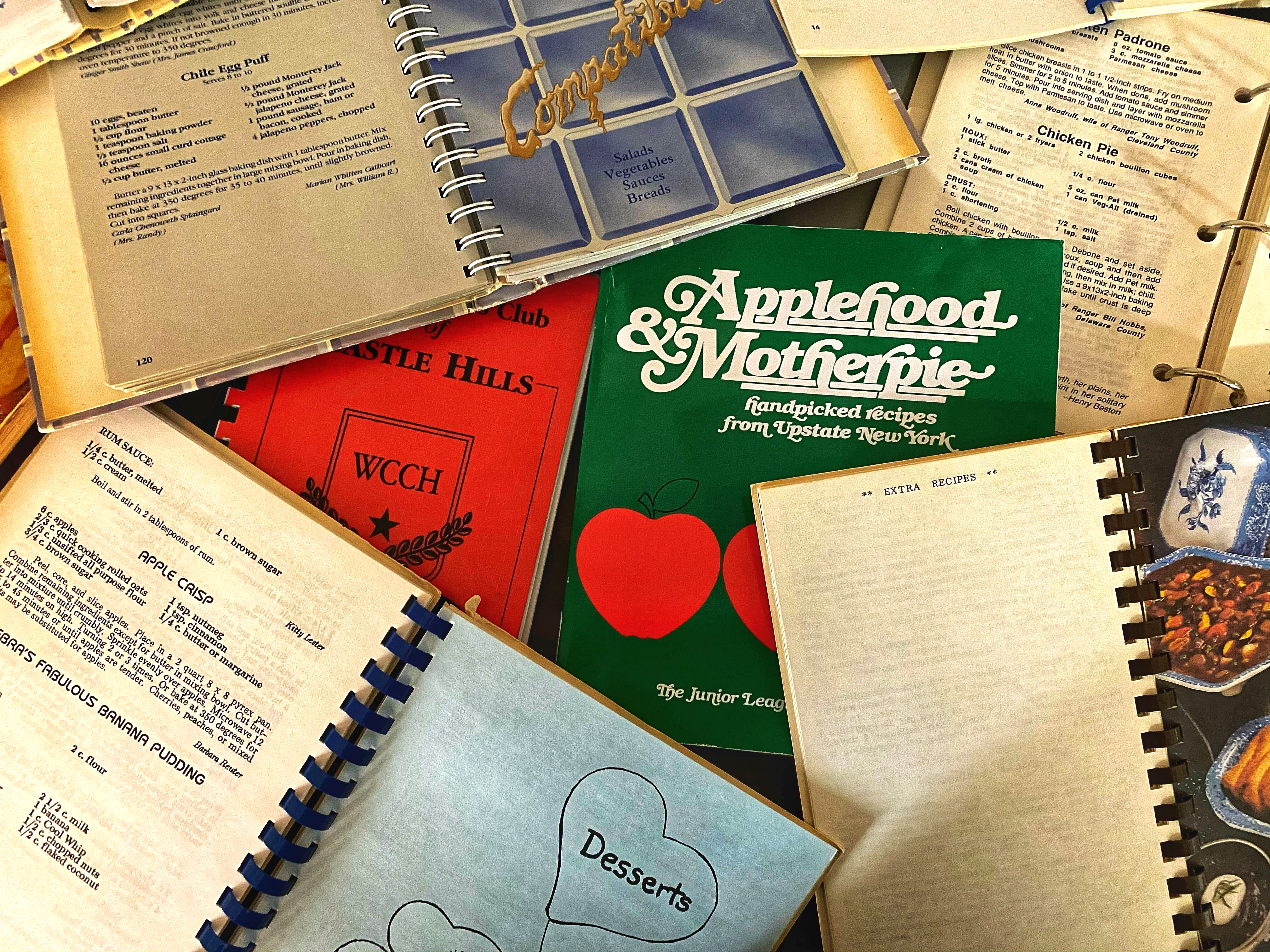 A pile of spiral-bound cookbooks, several open.