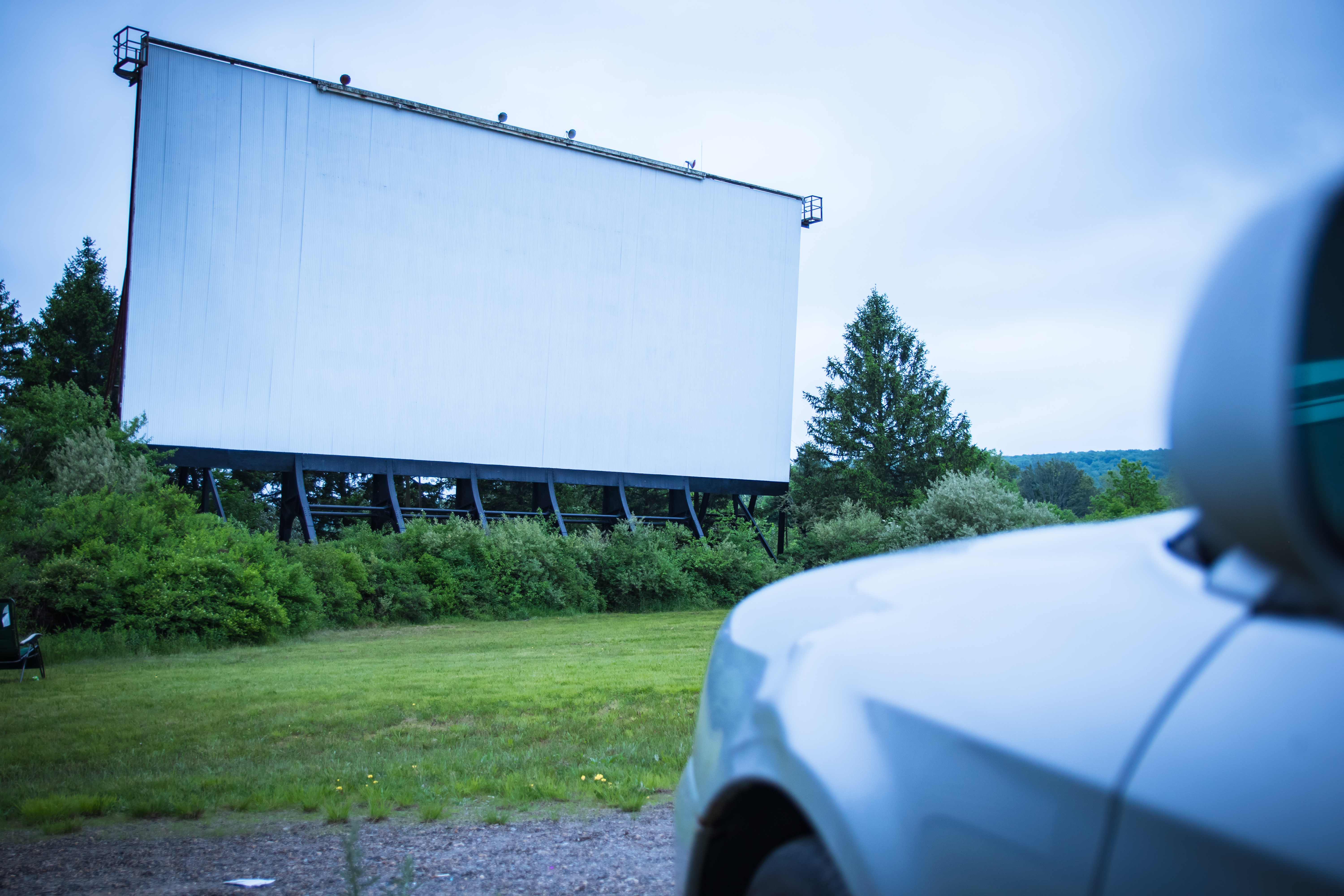 A large white movie screen set up outsides against green trees, and a car is in the right corner facing the screen