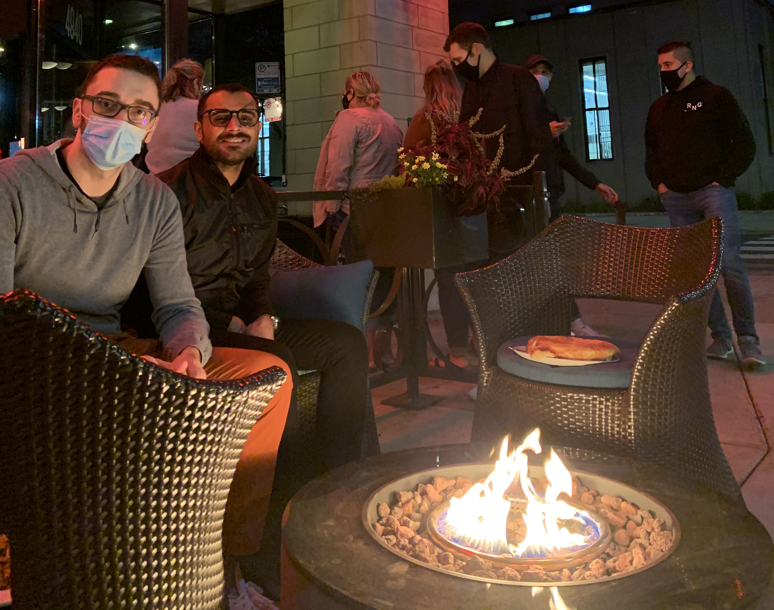Two people wearing masks at night around a fire pit.