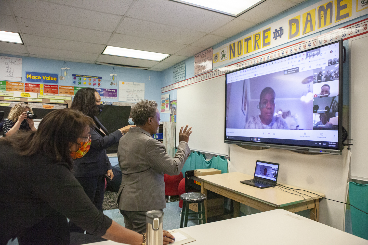 Mayor Lori Lightfoot talking to students over video chat on a large screen.