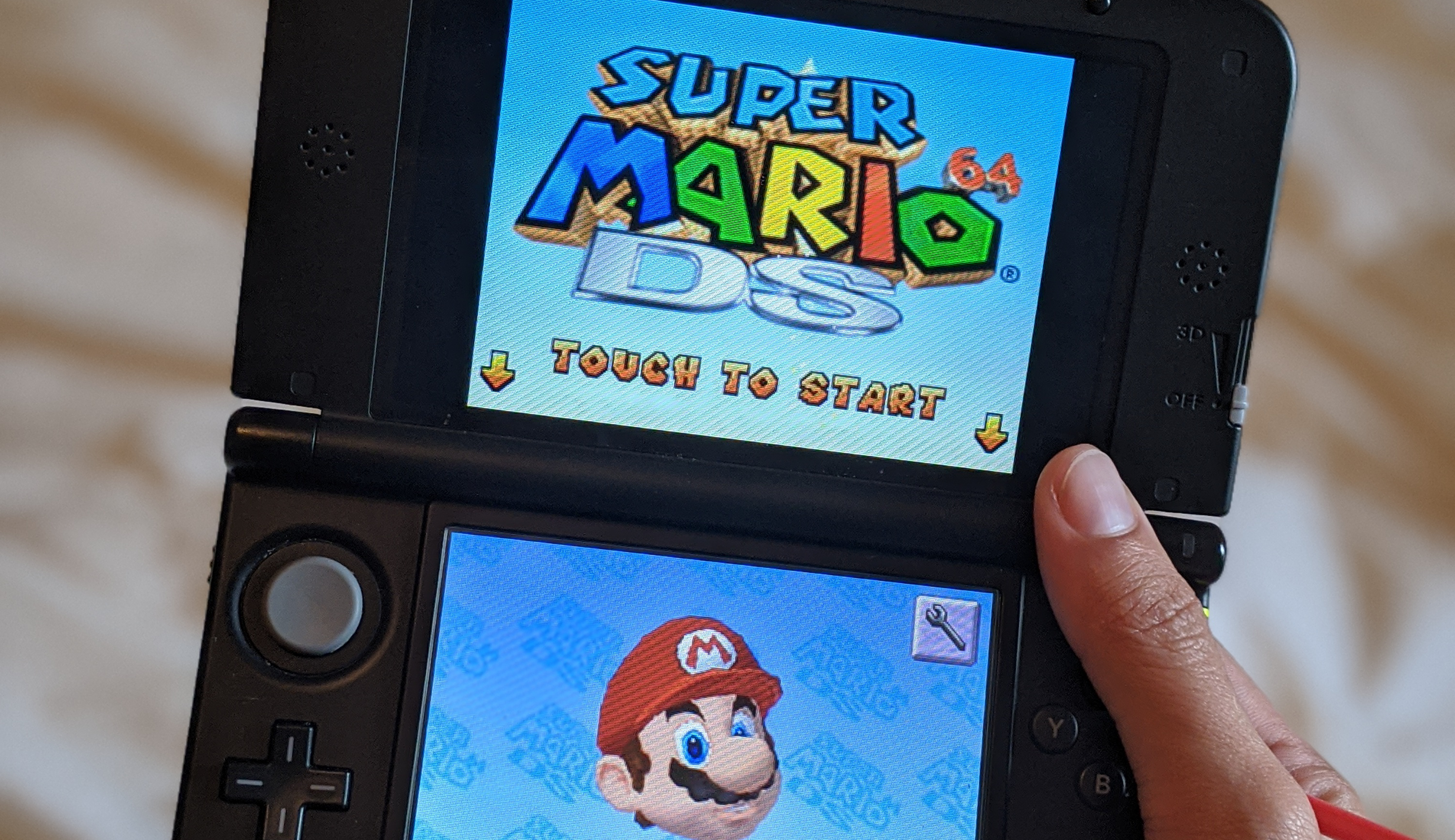 a person holding a Nintendo 3DS showing the Super Mario 64 DS start screen