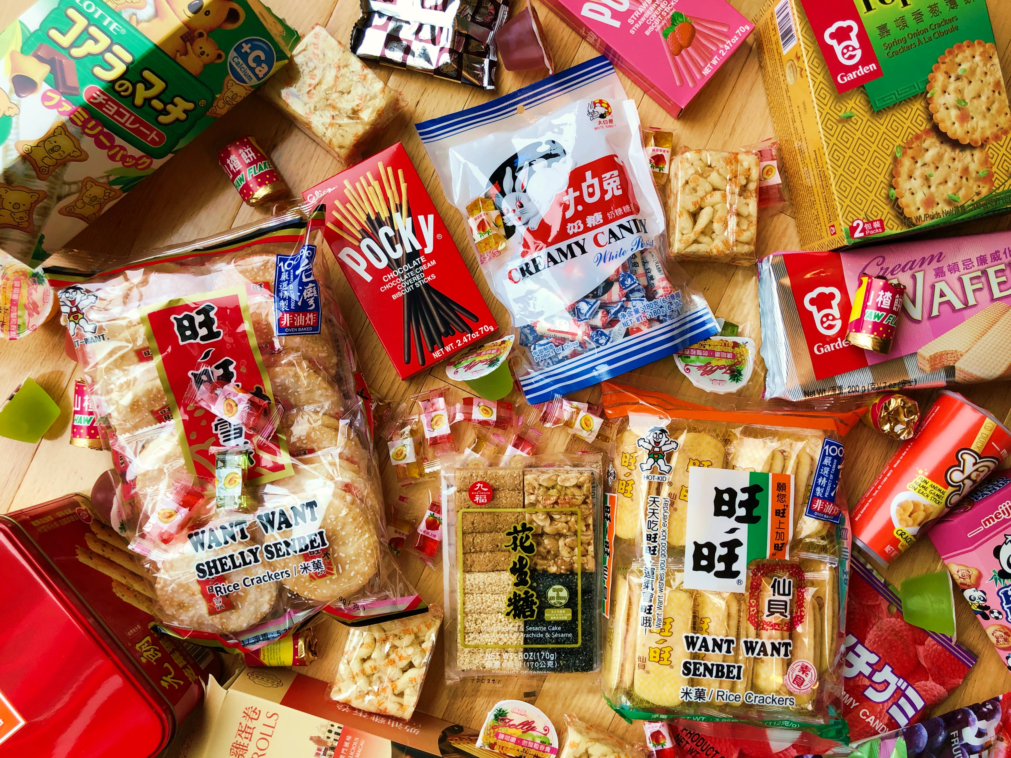 A top-down spread of Asian snacks, including Want Want rice crackers, Pocky, White Rabbit candy, sachima, wafers, crackers, fruit jelly and candy.