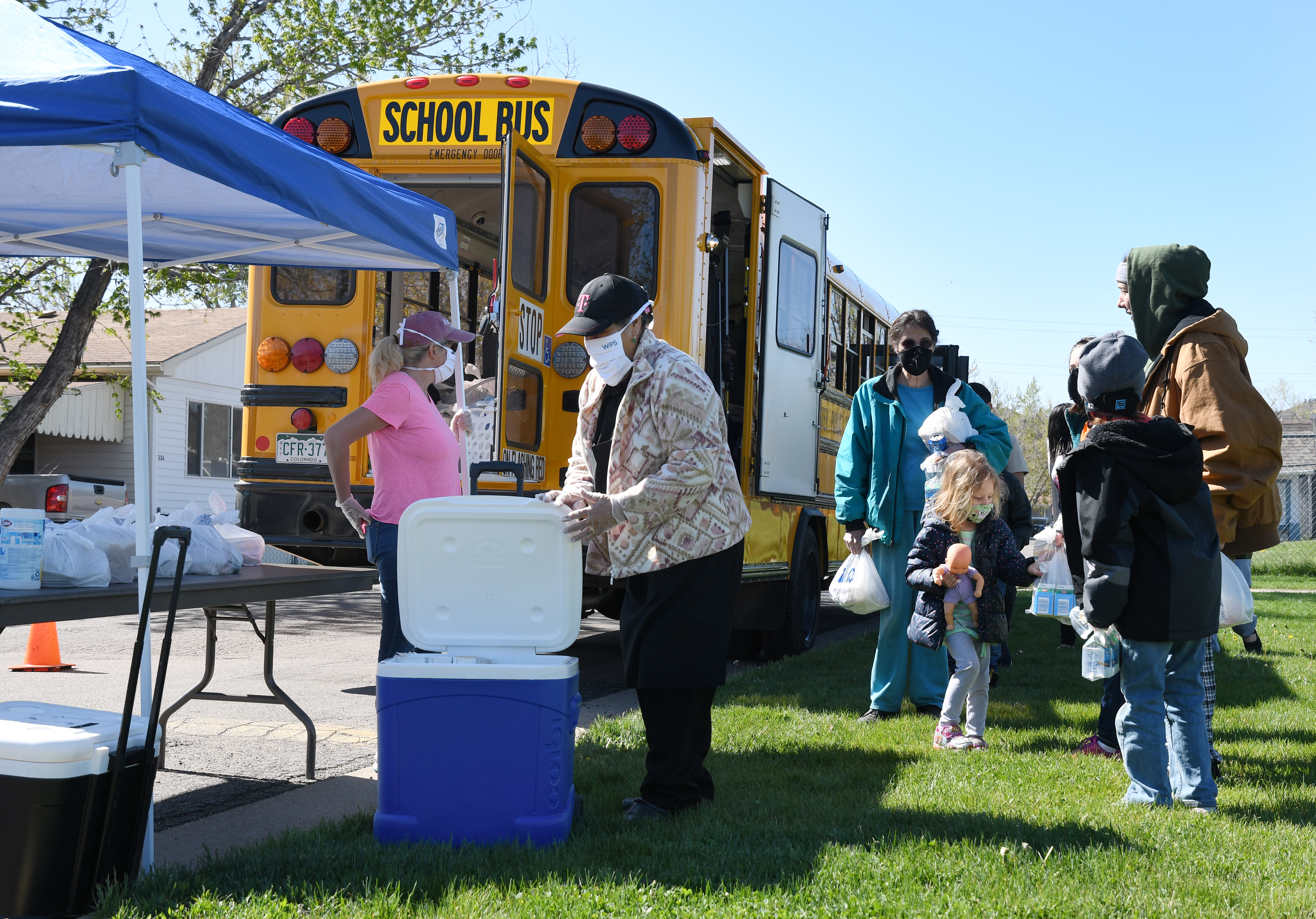 Children and adults wait for bagged food delivered by a school bus at Berkeley Village Mobile Home Park in Arvada, Colorado.