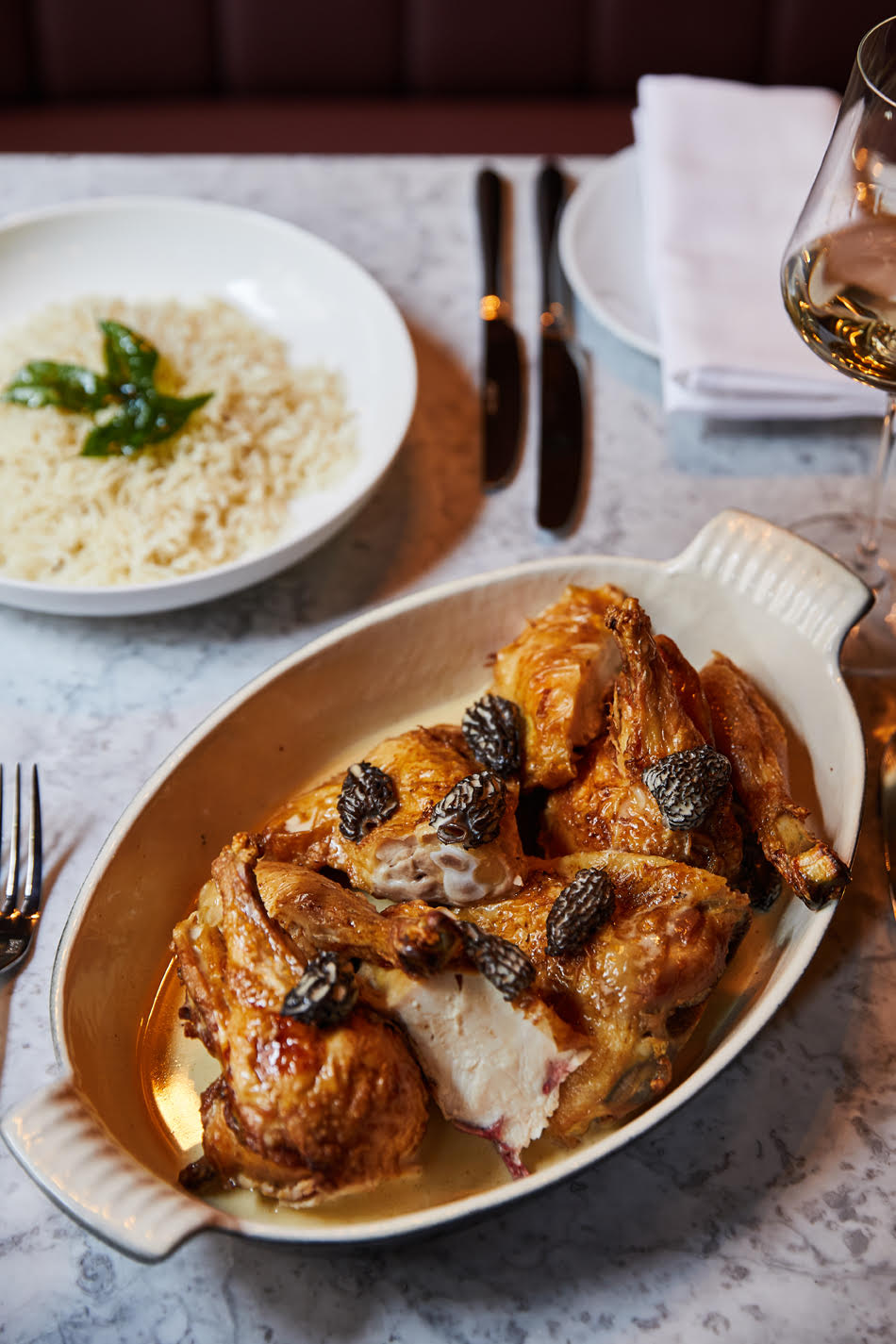 A dish of roast chicken with morel mushrooms in the foreground, on a marble table set with cutlery, and a plate of rice in the background