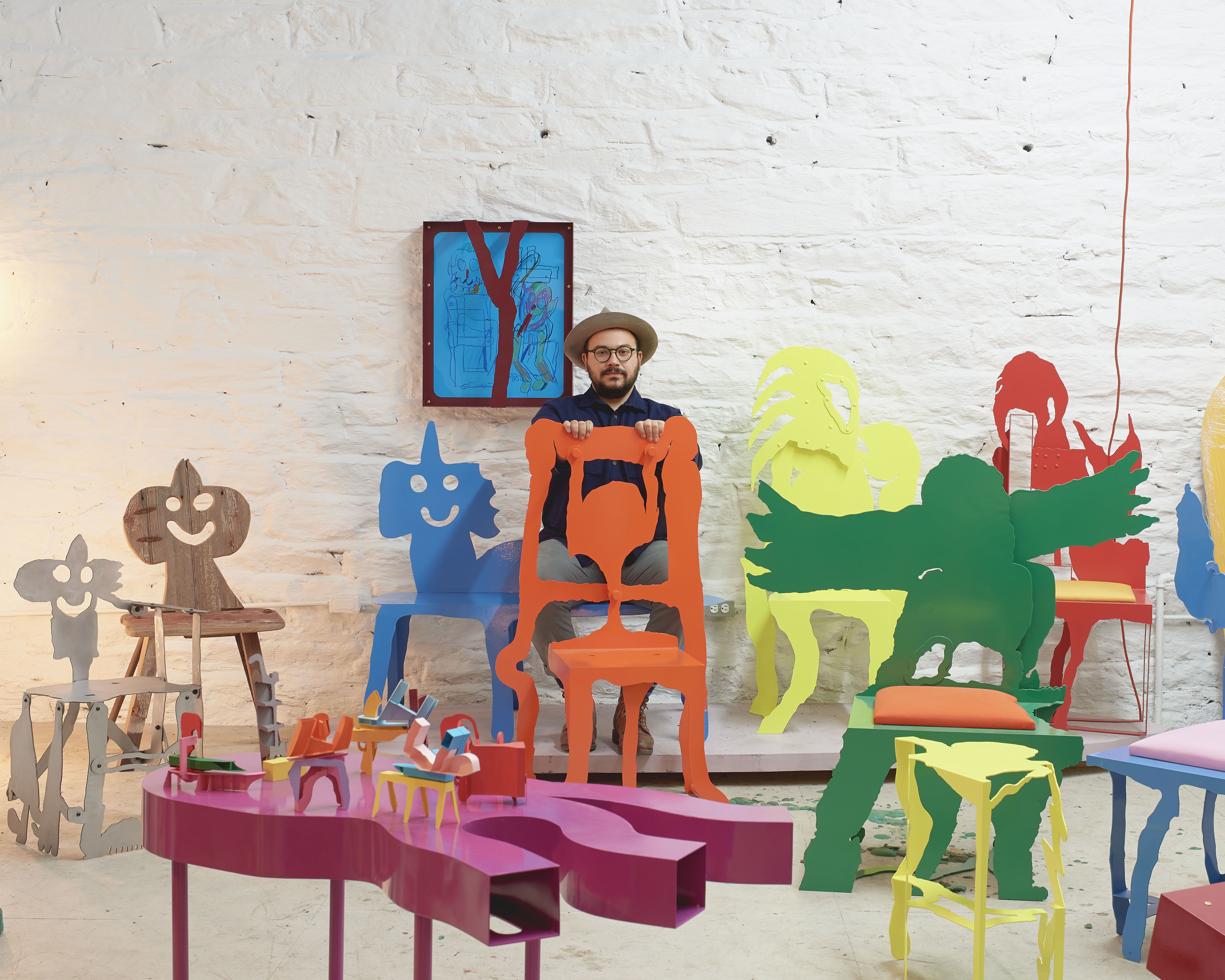 A man standing against a while wall with vibrantly colored furniture of his own designs in front of him