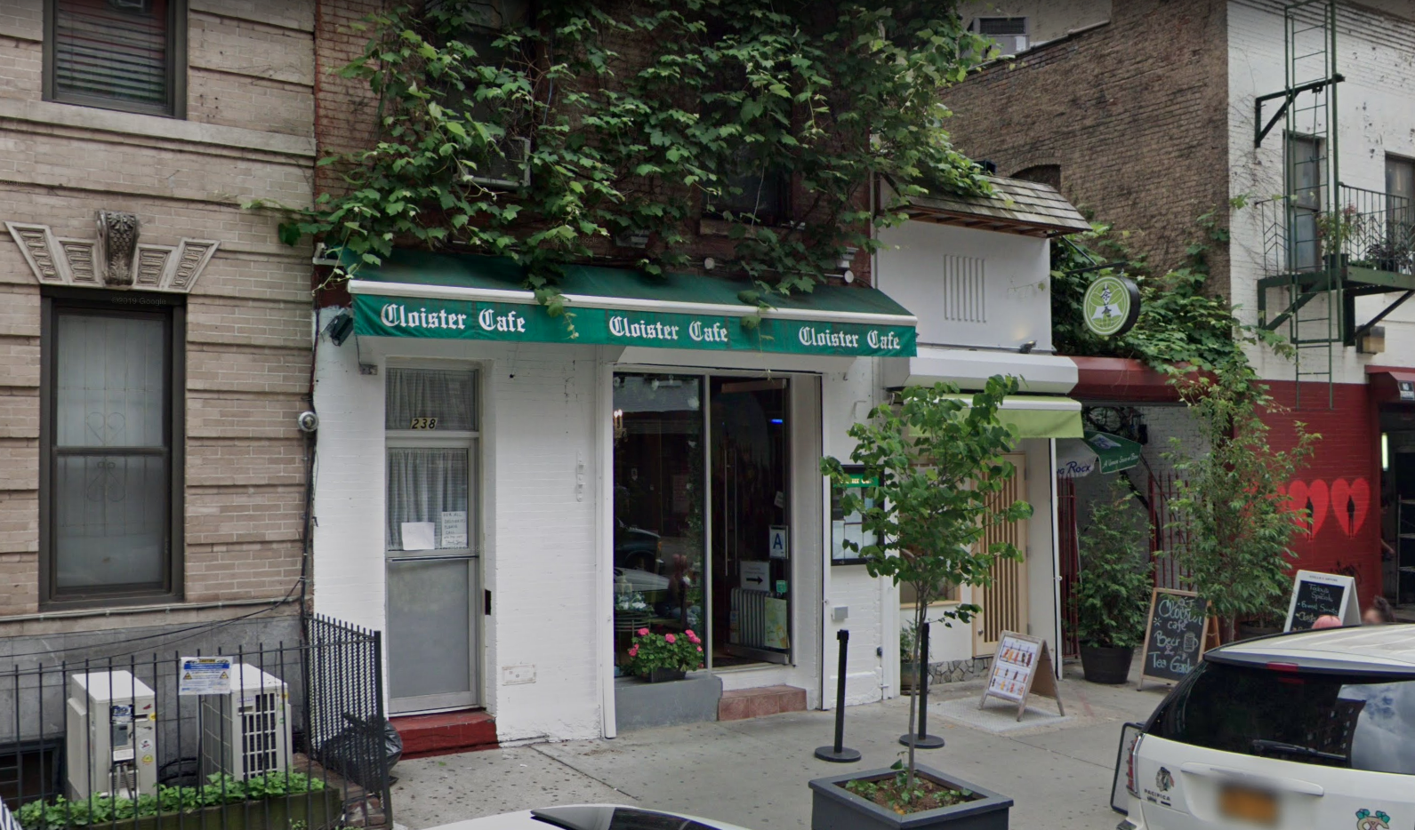 """A white facade with a green awning that reads """"Cloister Cafe"""" and ivy on the building"""
