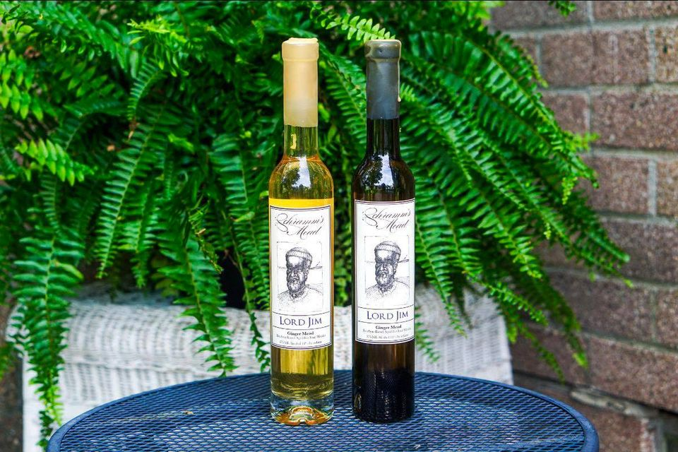 A bottle of yellow and a bottle of purple mead from Schramms sit on an iron patio table in front of a Fern.