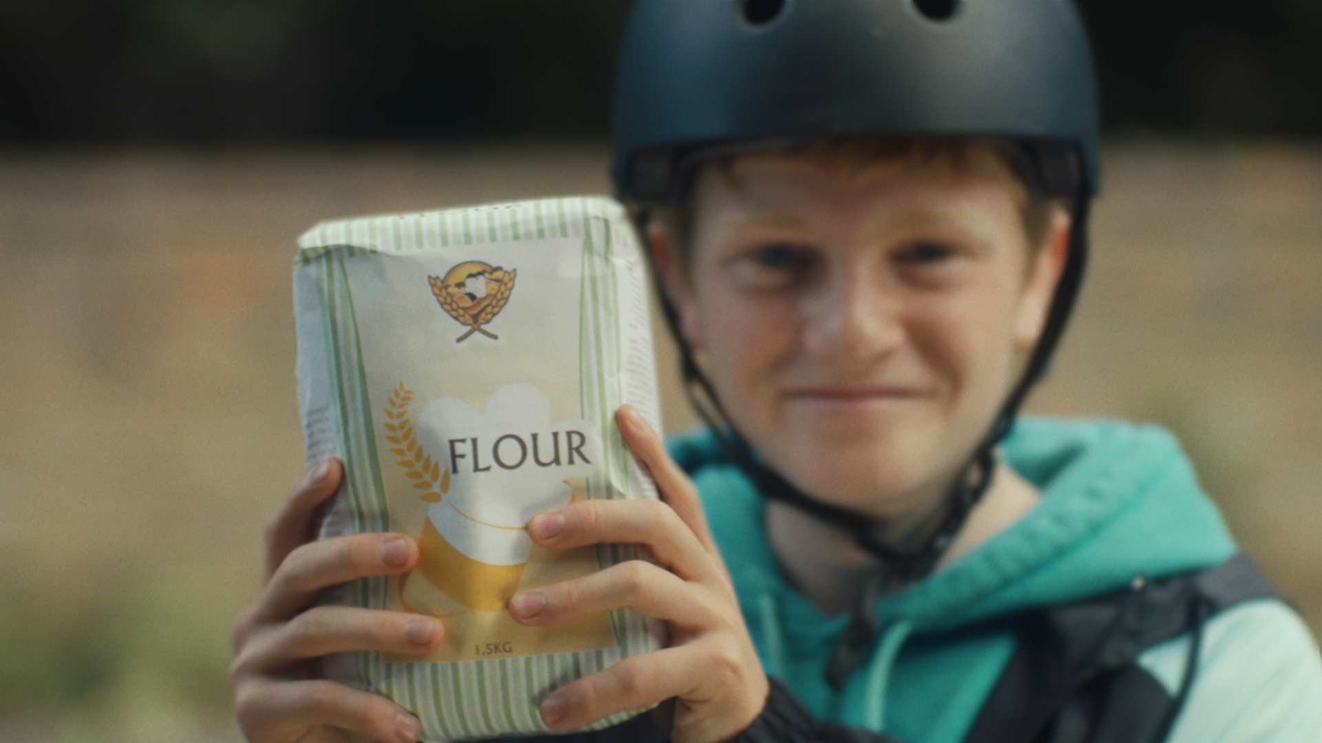 A still from the Great British Bake Off (GBBO) 2020 trailer shows a boy clutching a precious bag of four