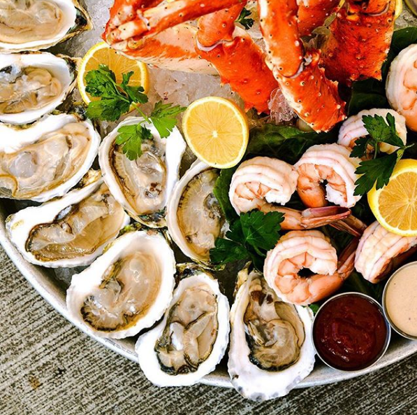A platter of raw oysters, shrimp, and crab legs with lemon wedges