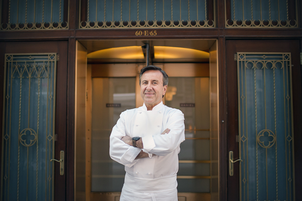 Chef Daniel Boulud stands with his arms crossed in chef's whites