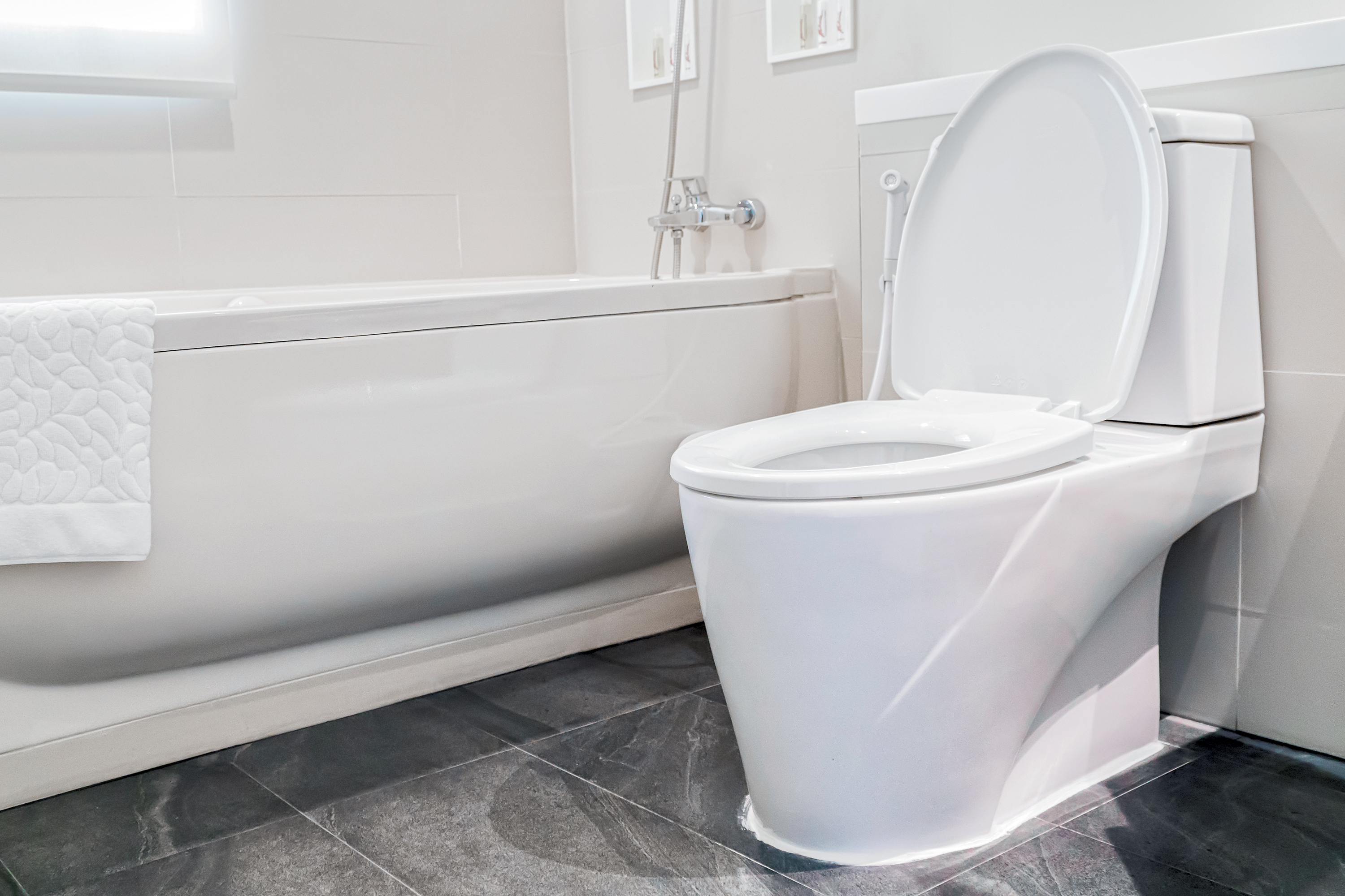 Toilet with lid up in a bright bathroom.