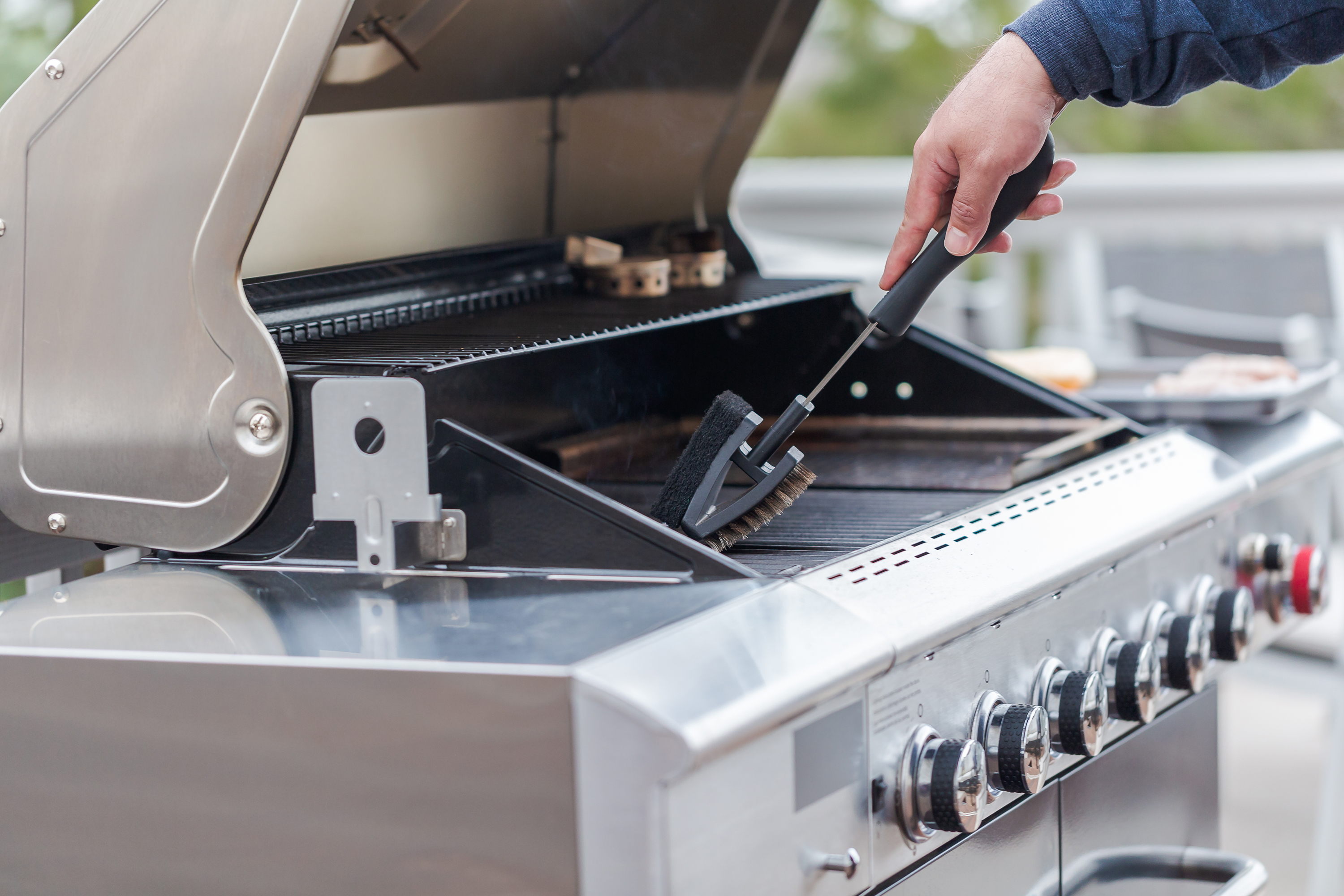 Man cleaning outdoor gas grill with brush.
