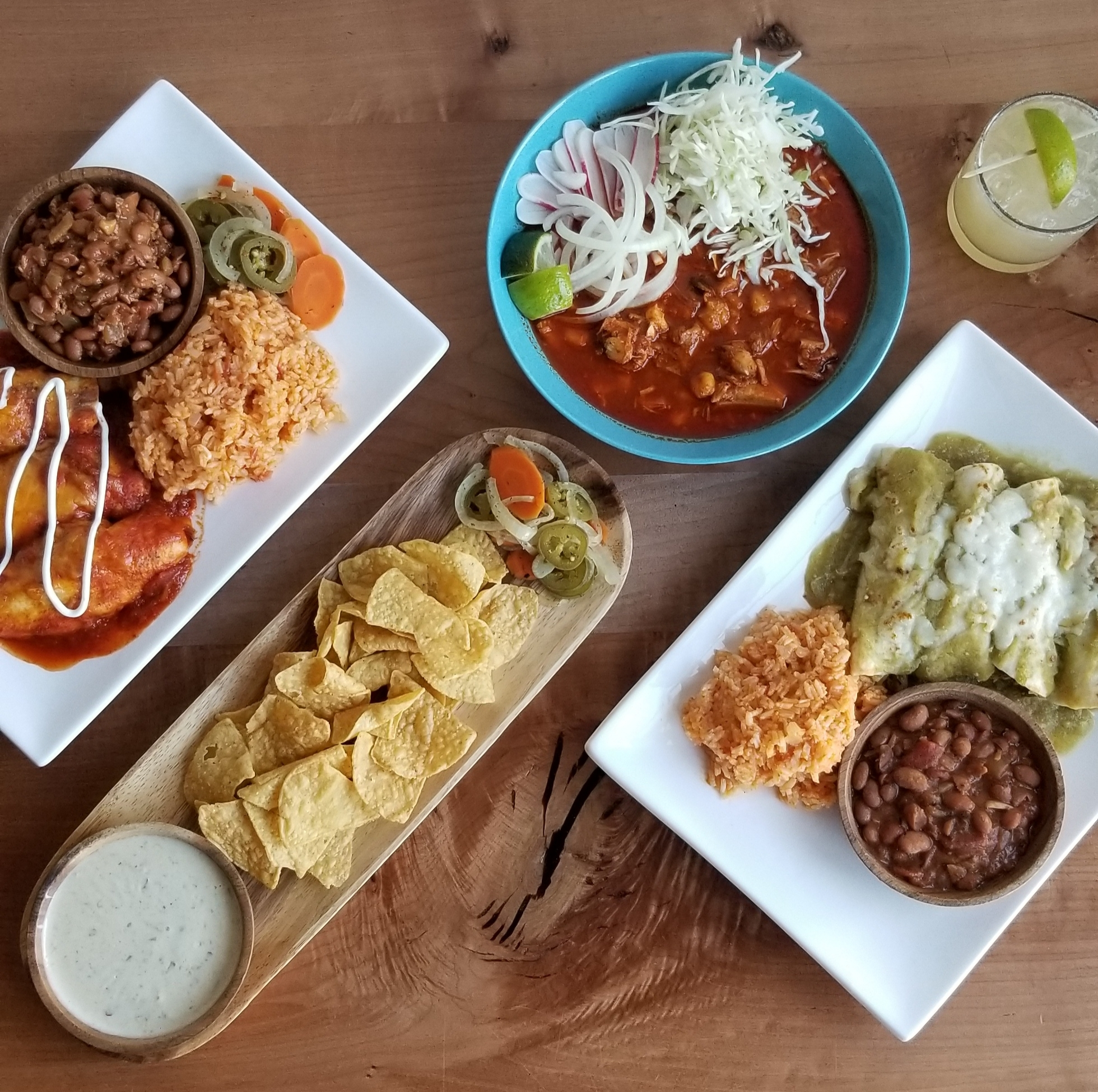A top-down view of enchiladas, nacho chips, and a variety of dips from Oaky's Tex Mex