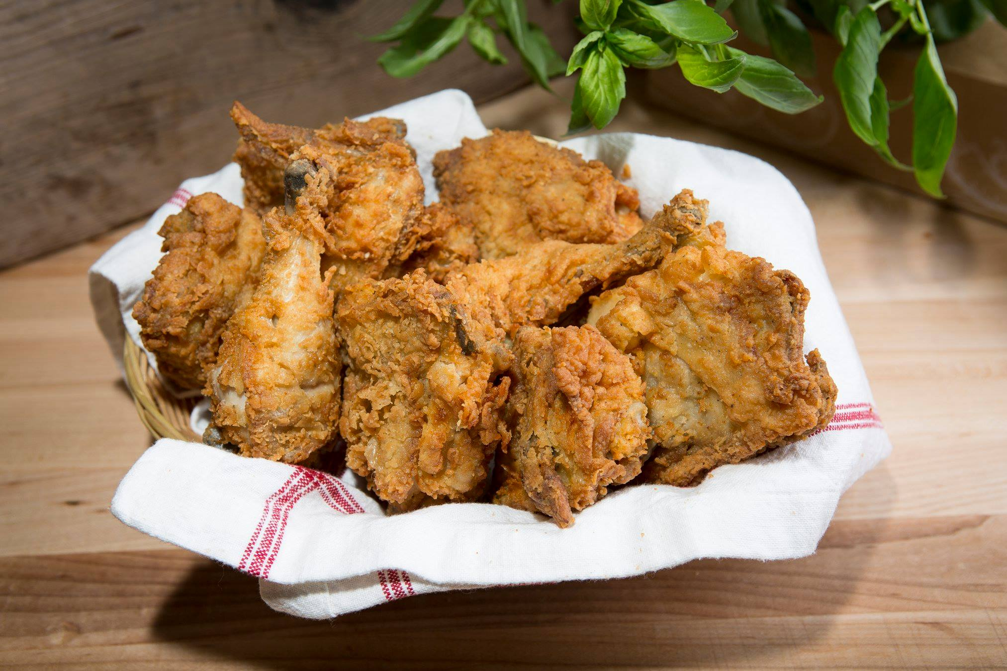 A basket of fried chicken with a white clothe underneath