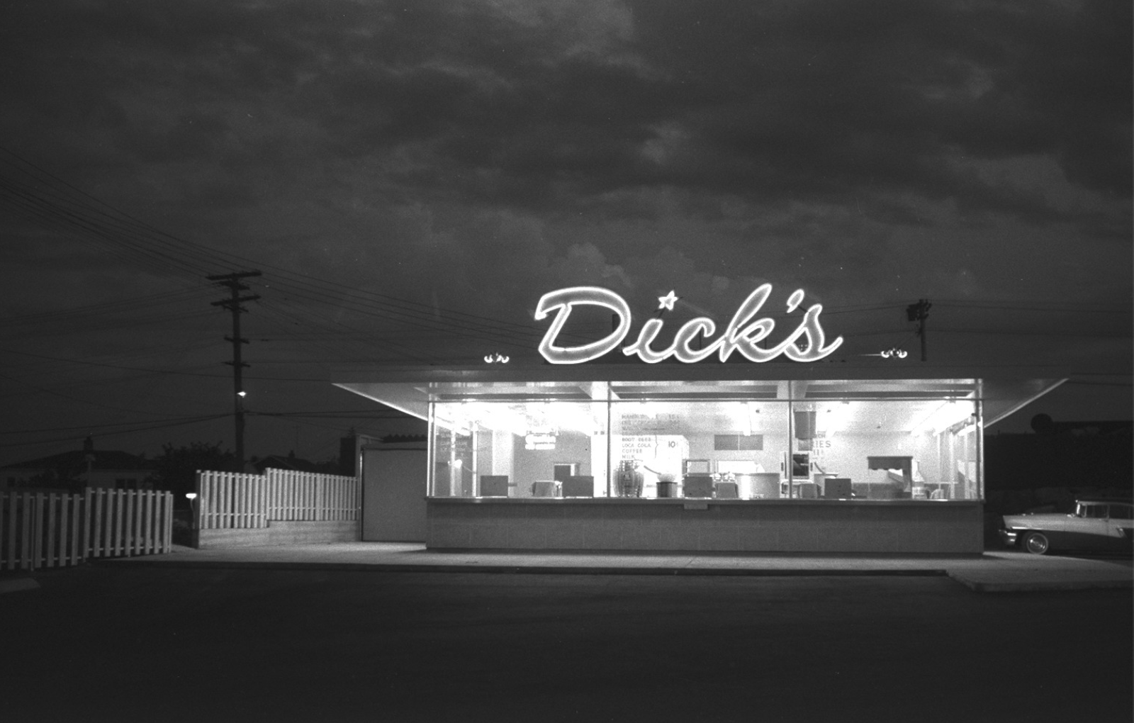 A black-and-white photo of the exterior of Dick's Drive-in, with a vintage car parked outside