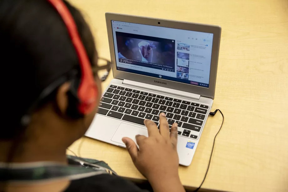 A student wearing headphones works on a laptop computer during a special education classroom exercise.