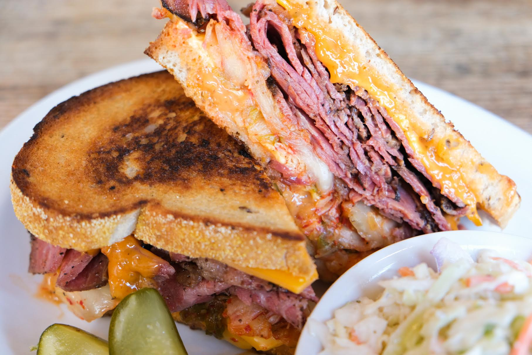 Two halves of a kimchi Reuben sandwich stacked on top of one another, with a small tub of coleslaw in the foreground