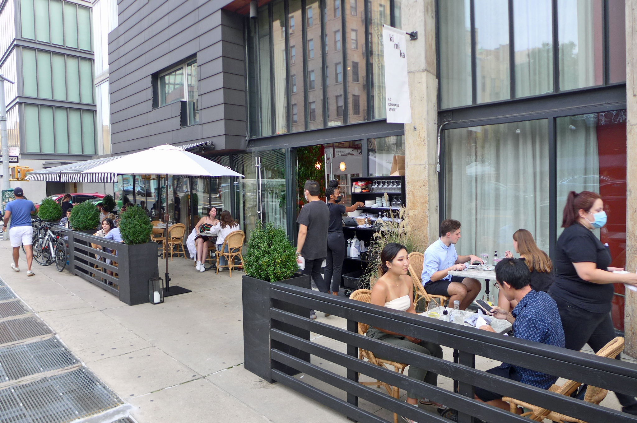 A black fence separates tables full of diners from the sidewalk, as a waitress in a mask walks out of the frame on the right.
