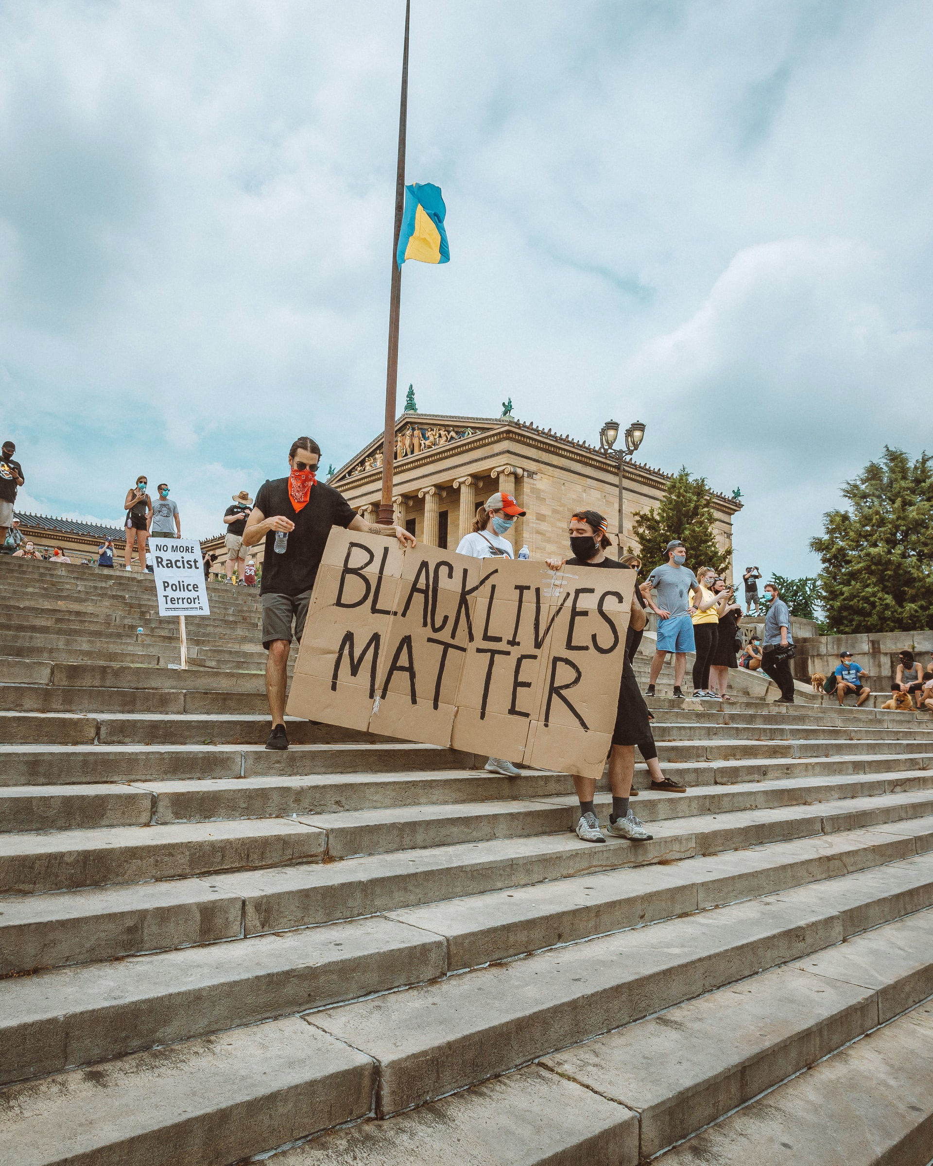 Protestors walking down the Art Museum steps holding a large cardboard sign that reads Black Lives Matter.