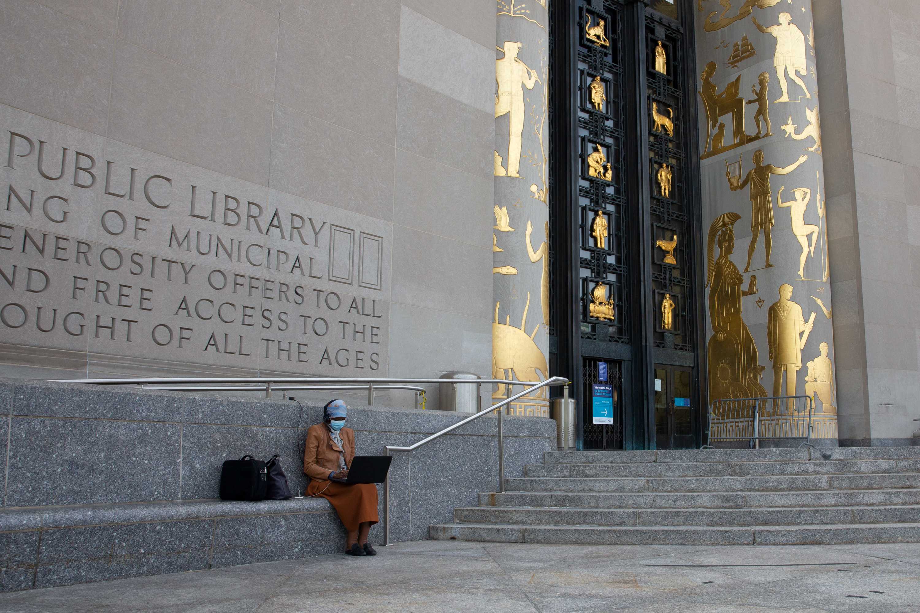 A woman uses free wifi from the Brooklyn Central Public Library, Sept. 14, 2020.