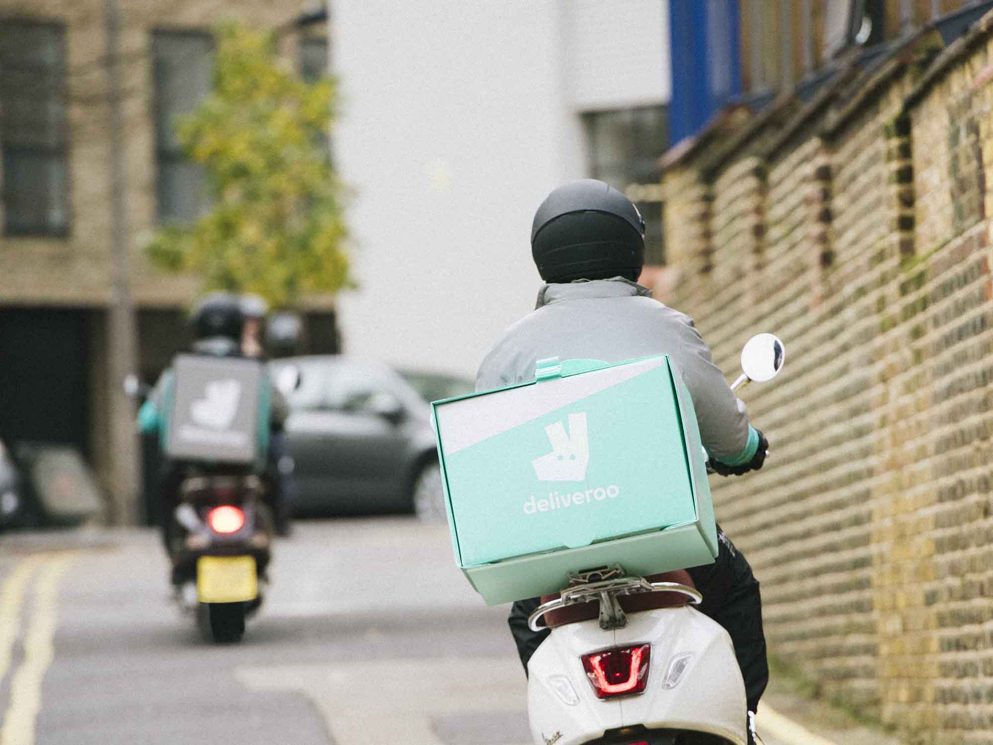 A Deliveroo rider in a Deliveroo jacket rides a motorbike in London