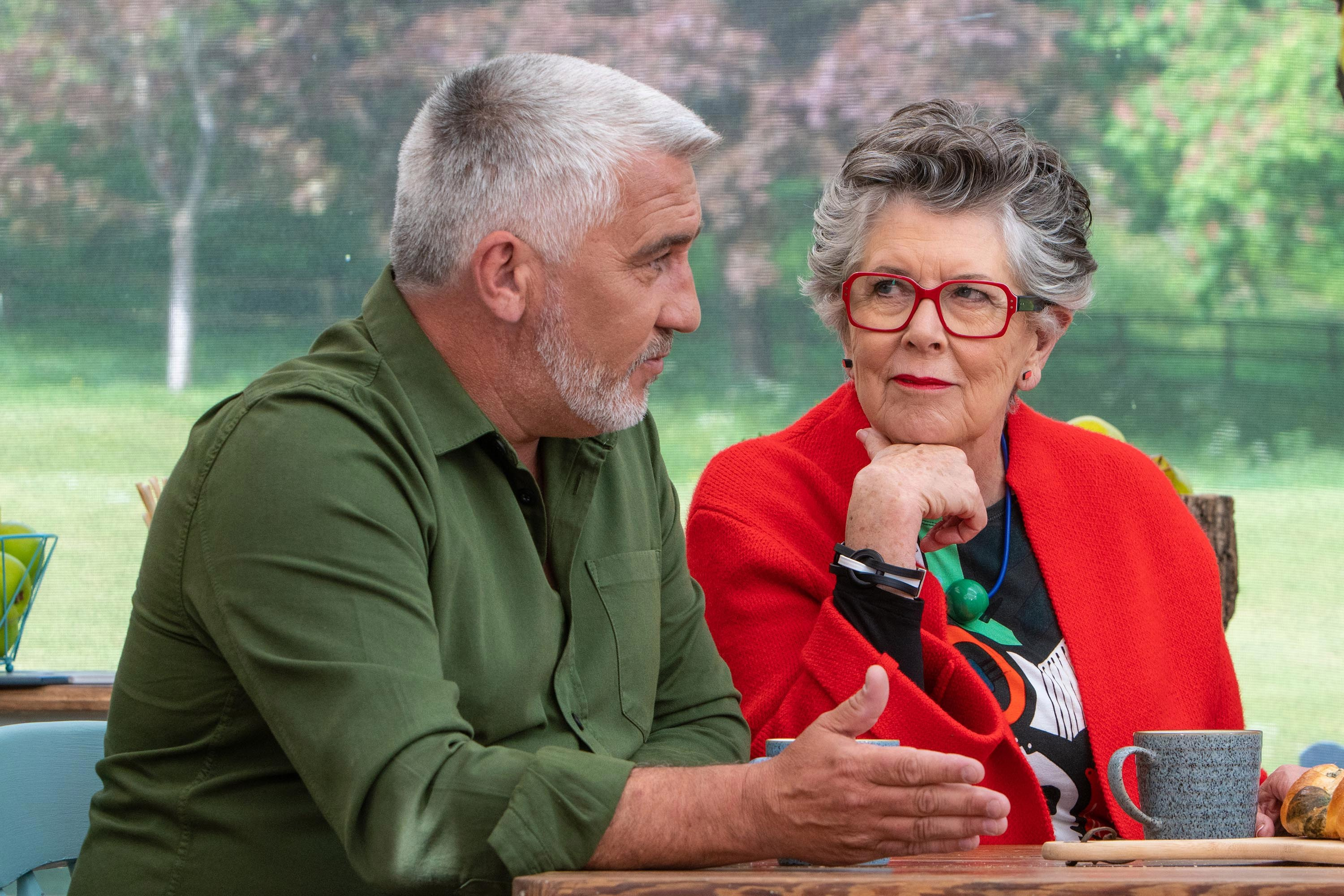 Paul Hollywood and Prue Leith sitting down, with Leith looking at Hollywood.