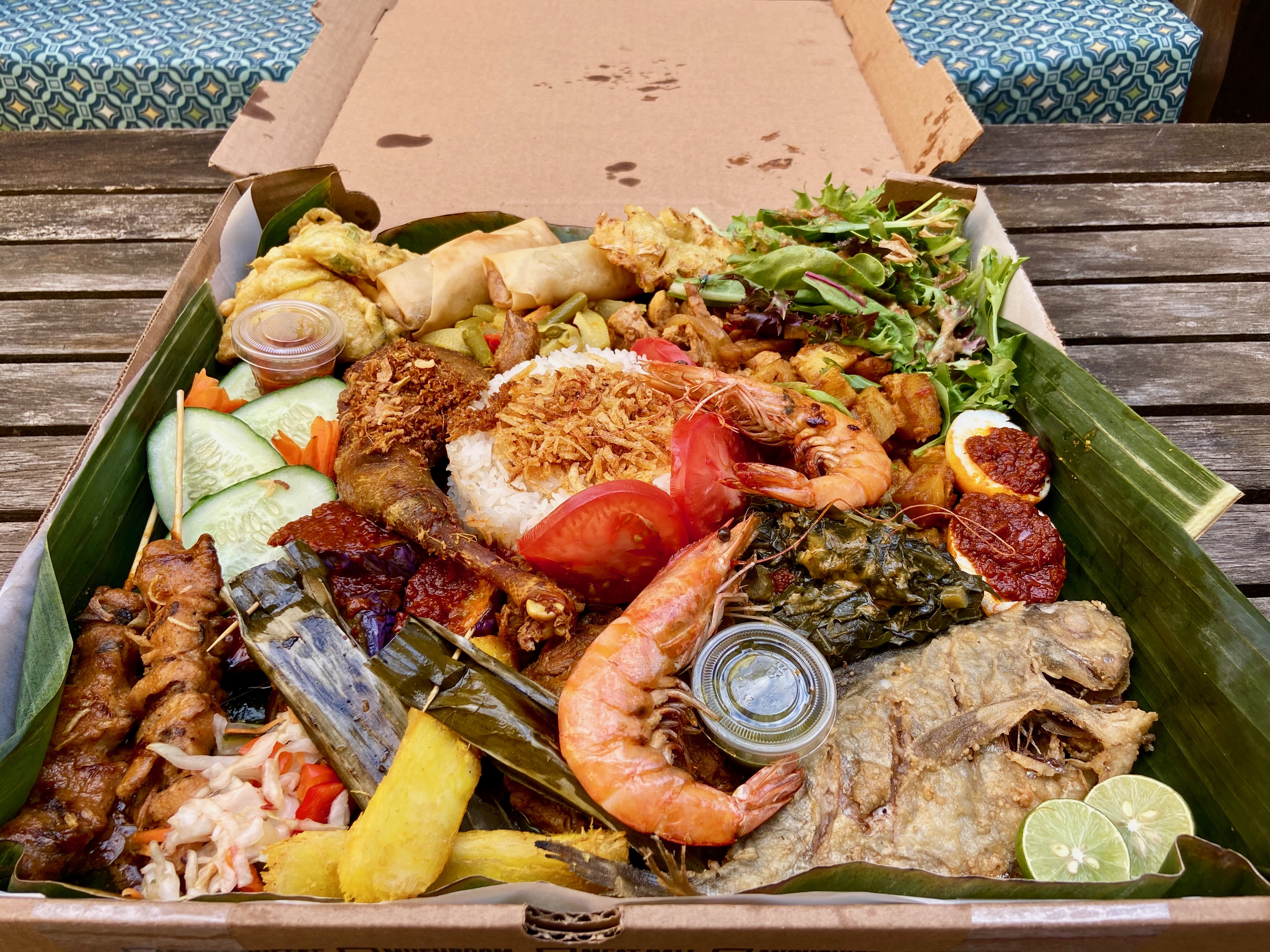 cardboard pizza box filled with indonesian dishes including rice, fried whole fish, and prawns