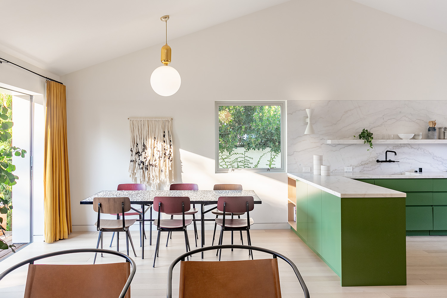 Bright living area with green kitchen cabinets and a six-seat dining set.