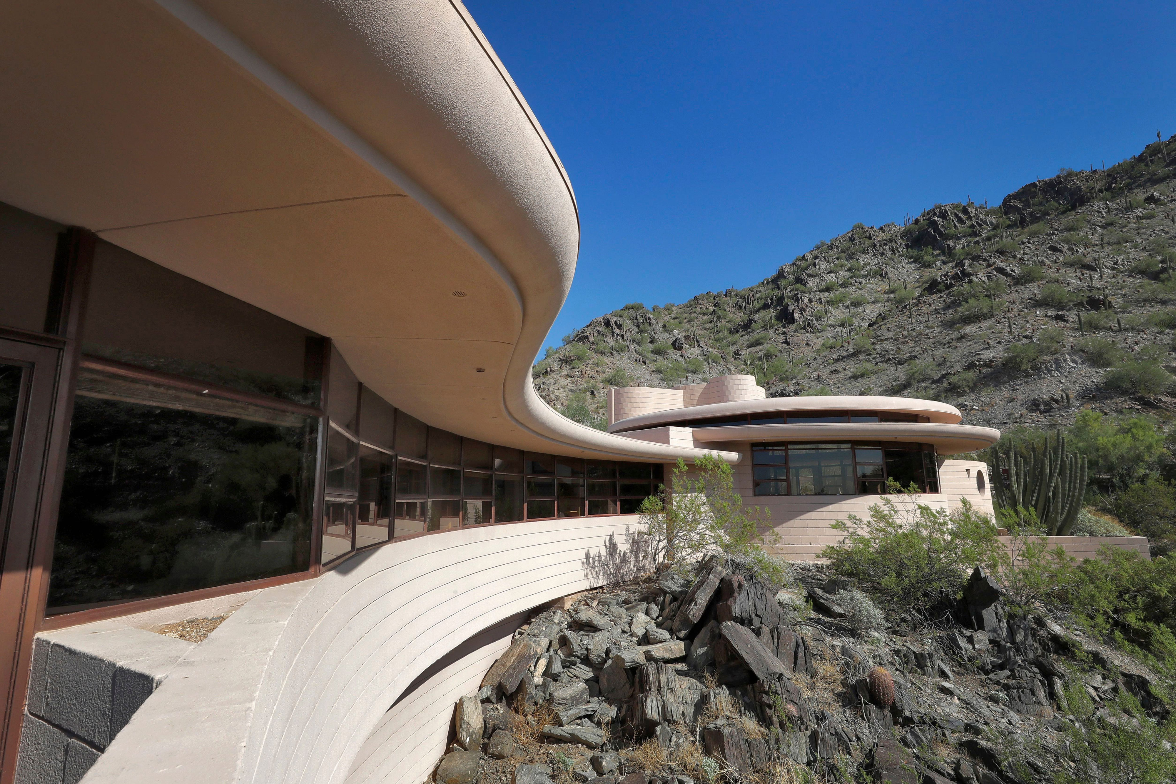 Frank Lloyd Wright's Norman Lykes house in Phoenix, Arizona, which just went back on the market for $8M. The exterior shows a swooping curved patio towards a circular room.