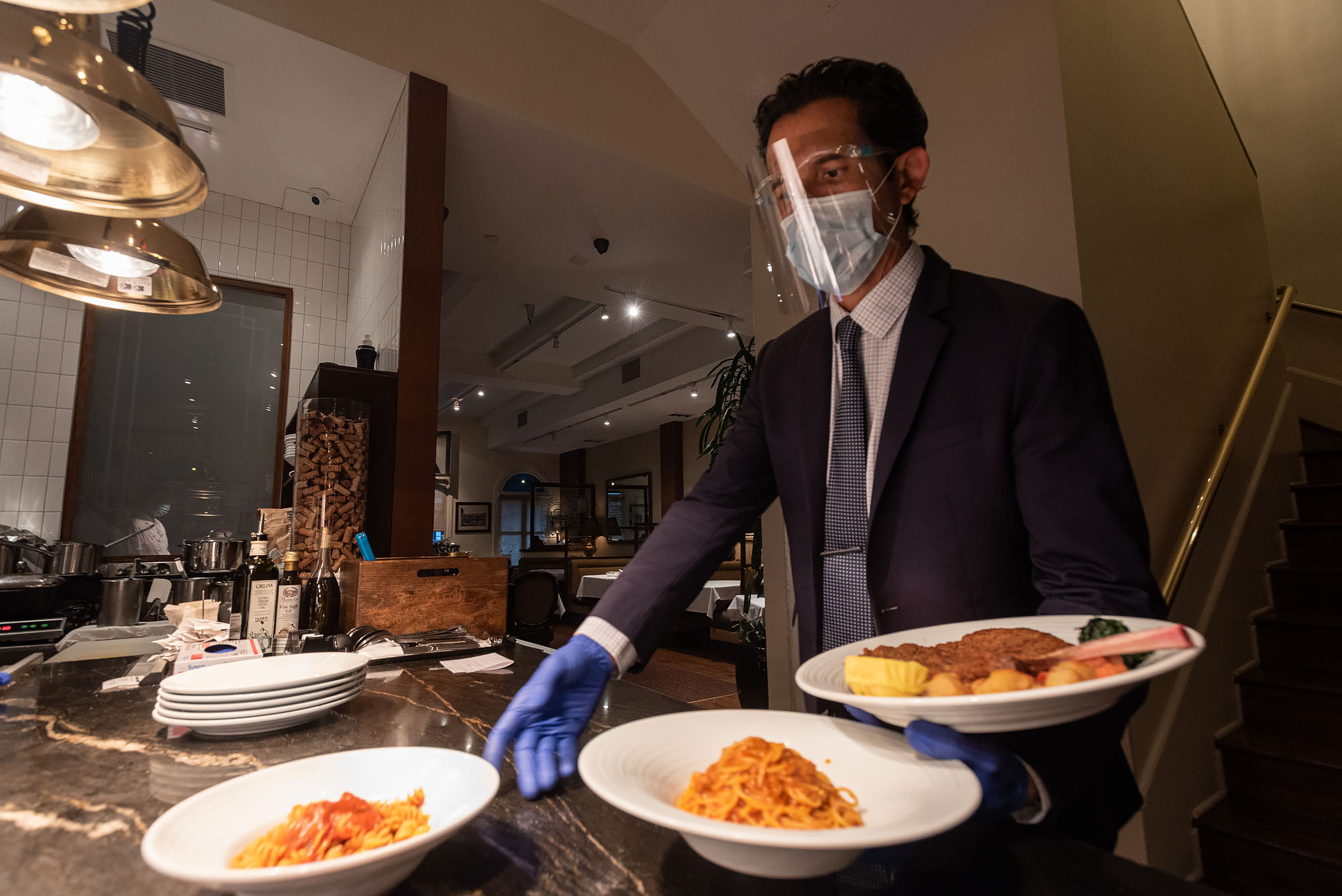 A worker in a suit with a plastic shield and face mask grabs plates of Italian food.